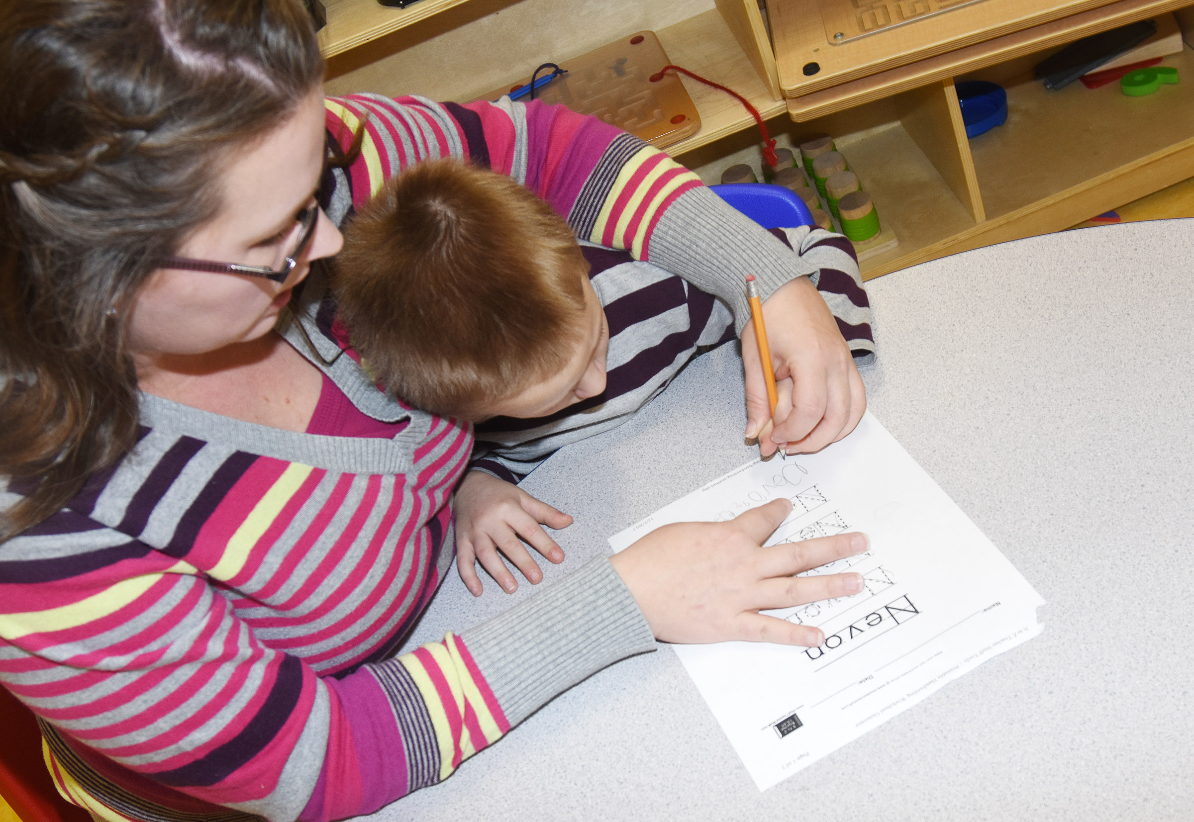 CES preschool assistant Jessica Williams helps Nevon Stum write his name.