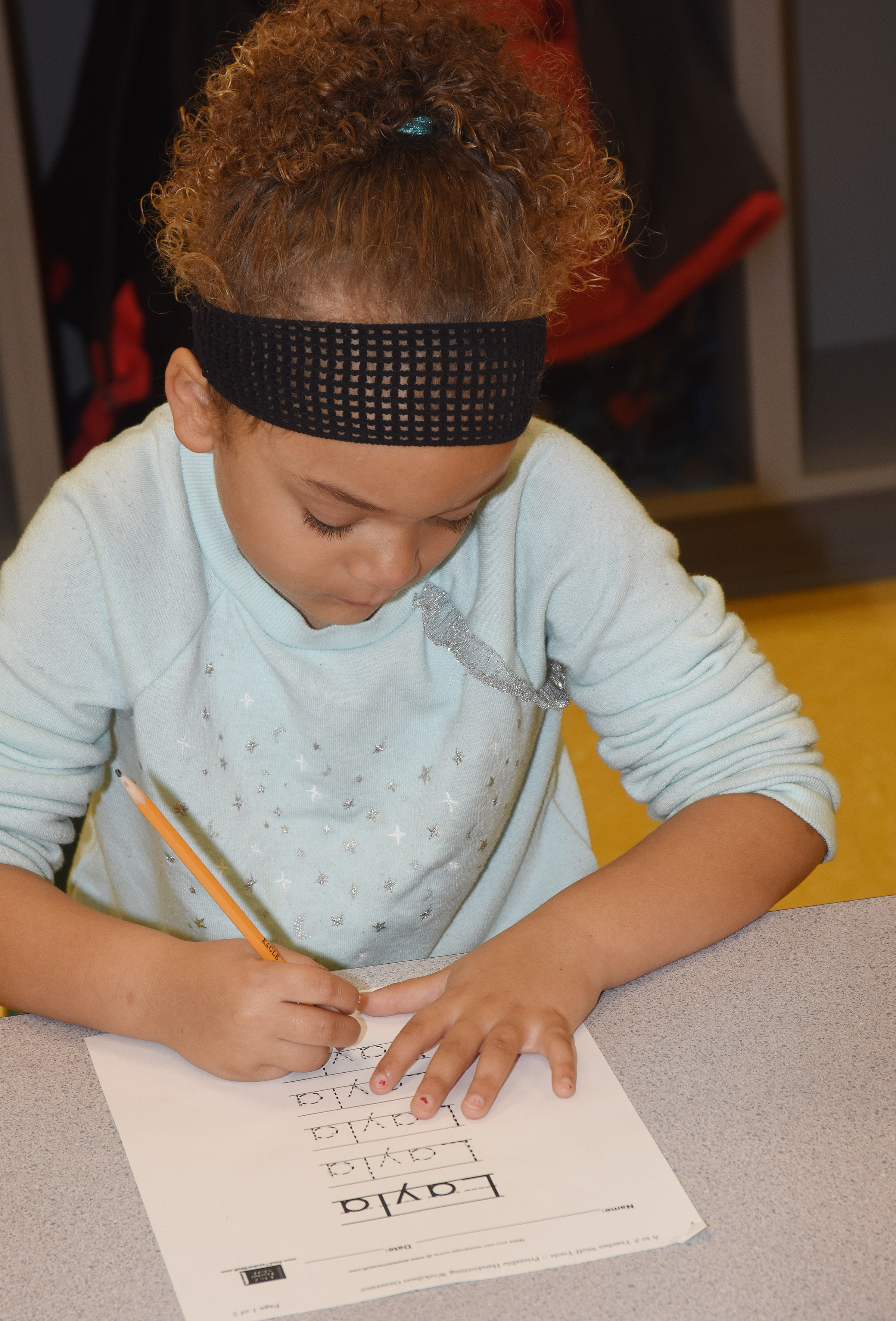 CES preschool student Layla Barbee writes her name.