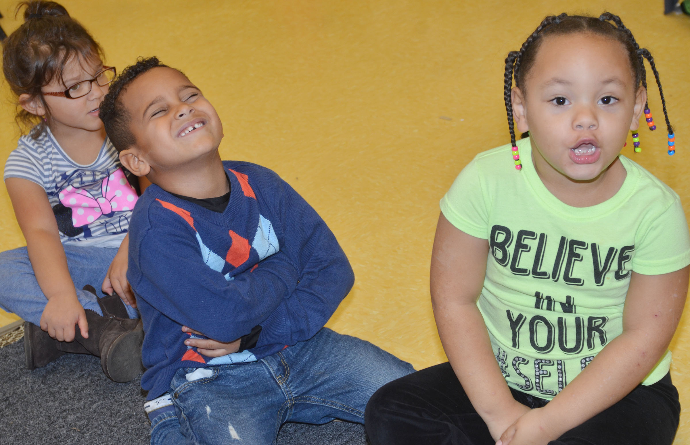 From left, CES preschool students Addisyn Taylor, Kingston Cowherd and Lillian Merriweather laugh as they sing together.