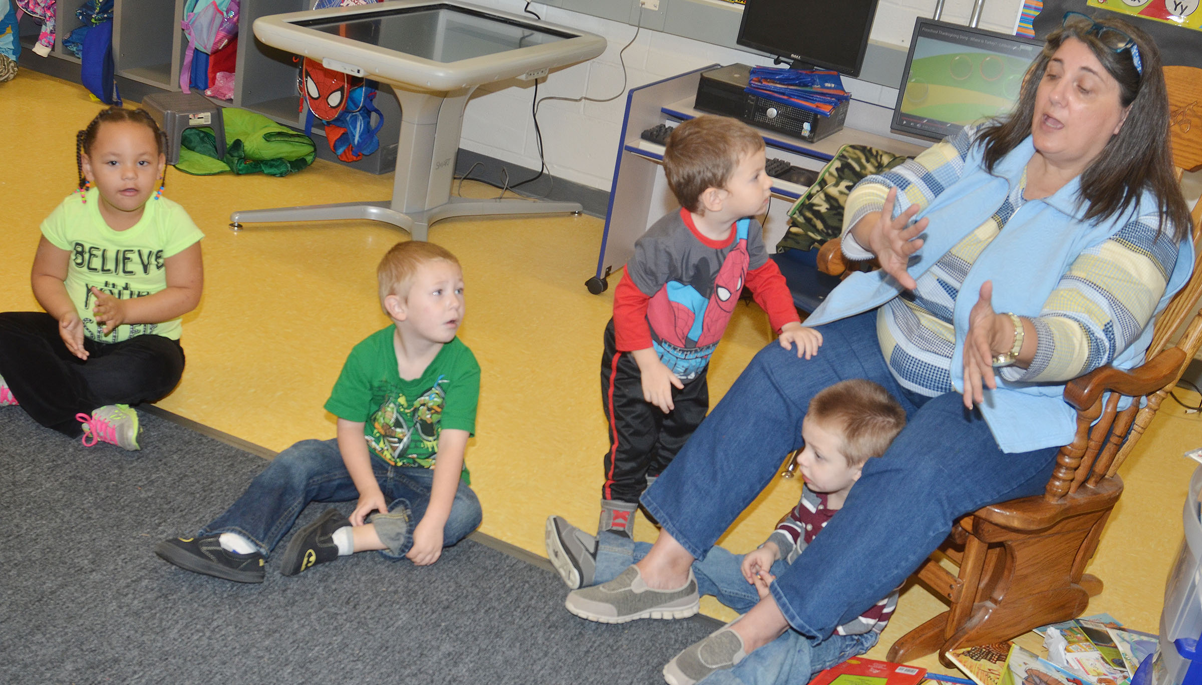 CES preschool teacher Sherry Cowherd sings with her students.
