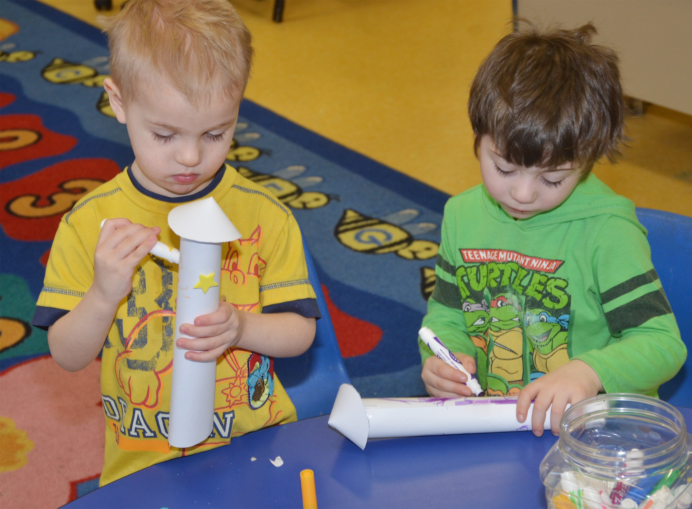 CES preschool students Chase Russell, at left, and Josiah Dean decorate their rockets.