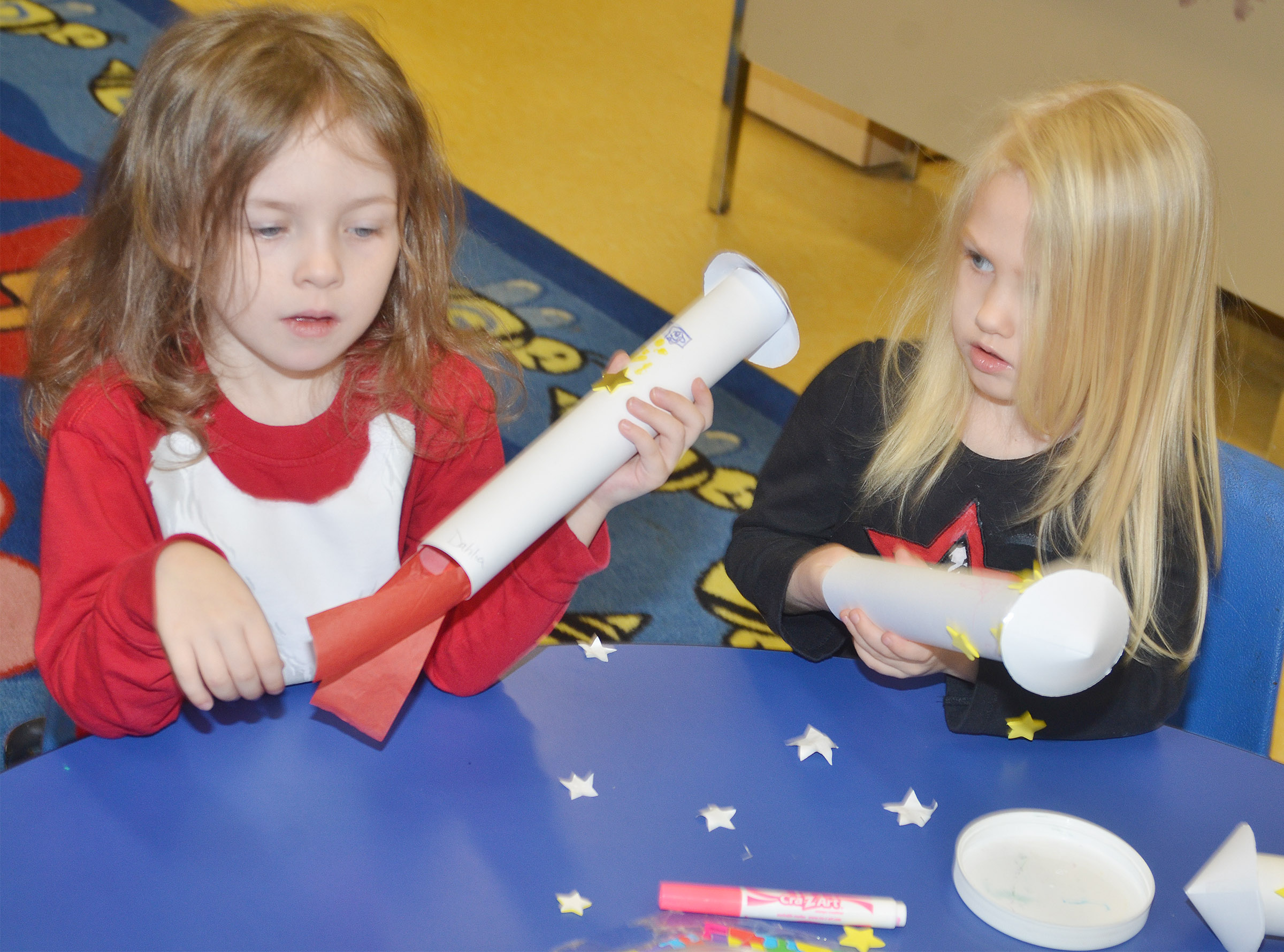 CES preschool students Dahlia Ward, at left, and Trinity Lewis decorate their rockets.