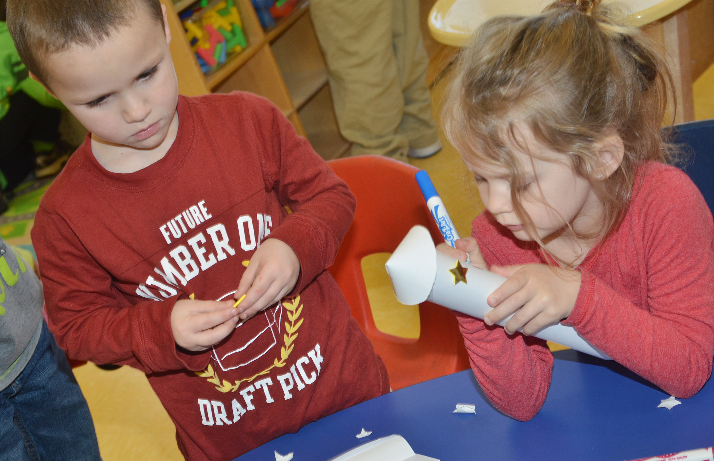 CES preschool students Triton Bradshaw, at left, and Dahlia Ward decorate their rockets.