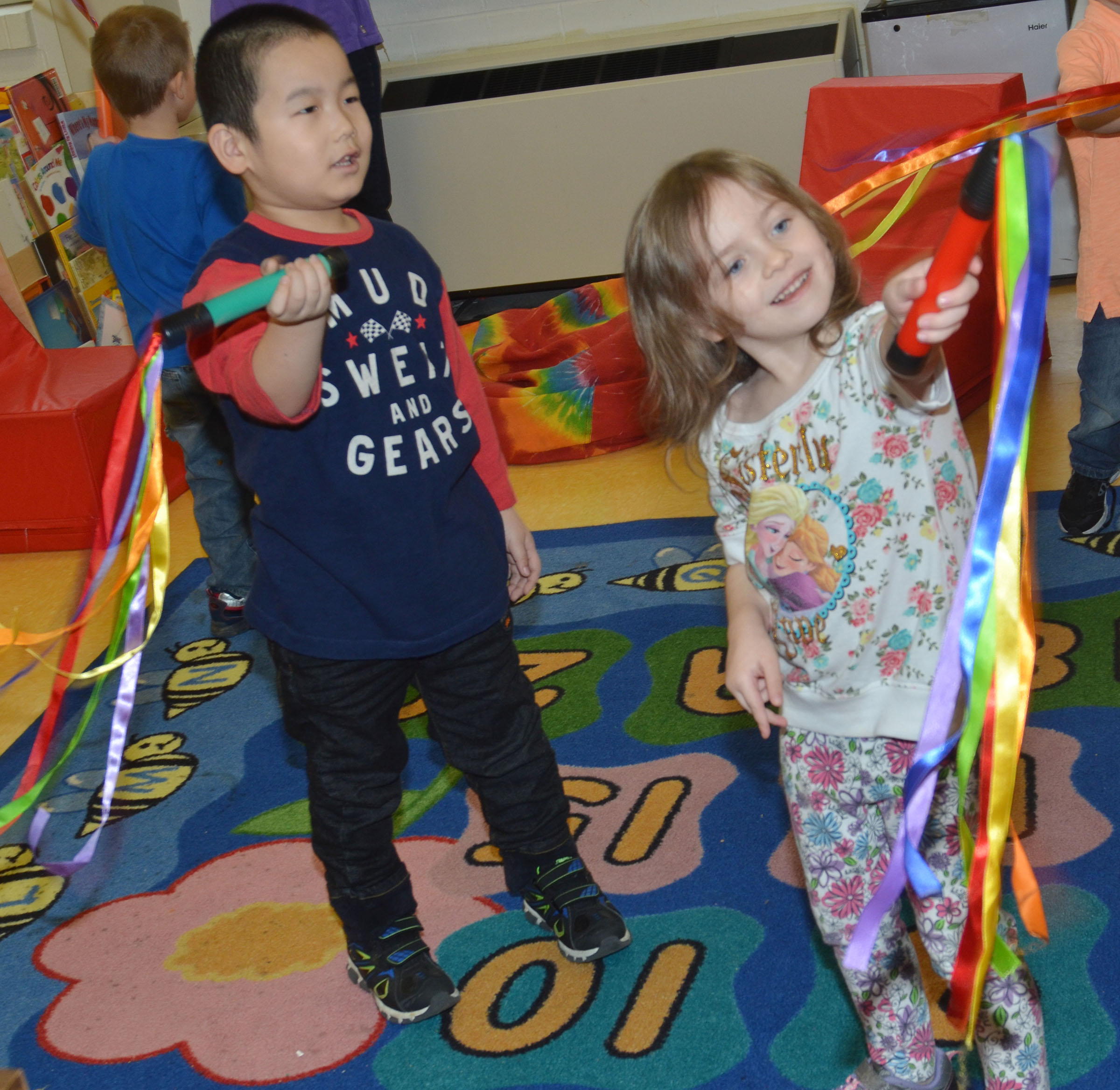 CES preschool students Calvin Yang, at left, and Dahlia Ward dance with their ribbons.
