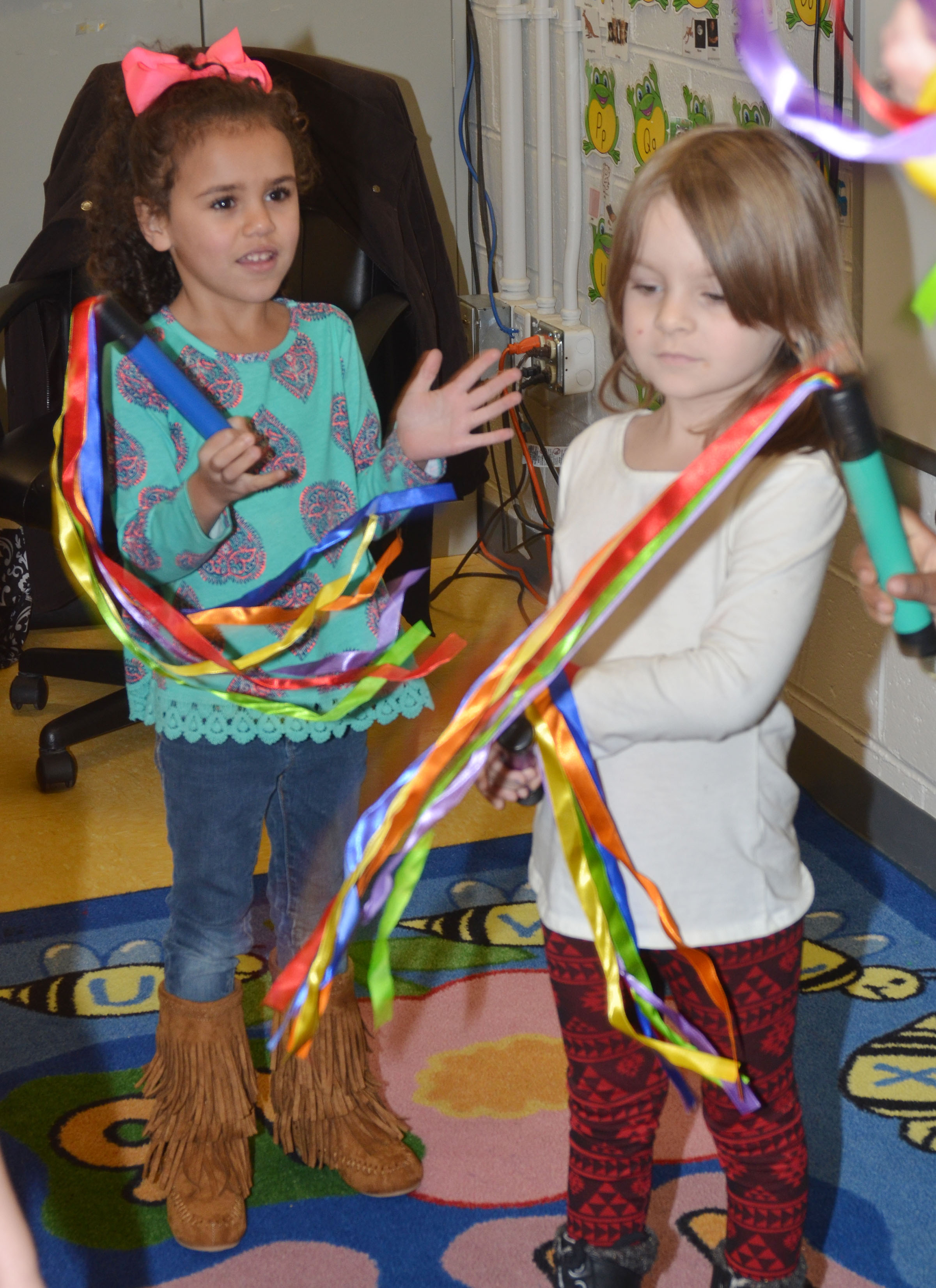 CES preschool students Adelyn Litsey, at left, and Daisy Rakes dance with their ribbons.