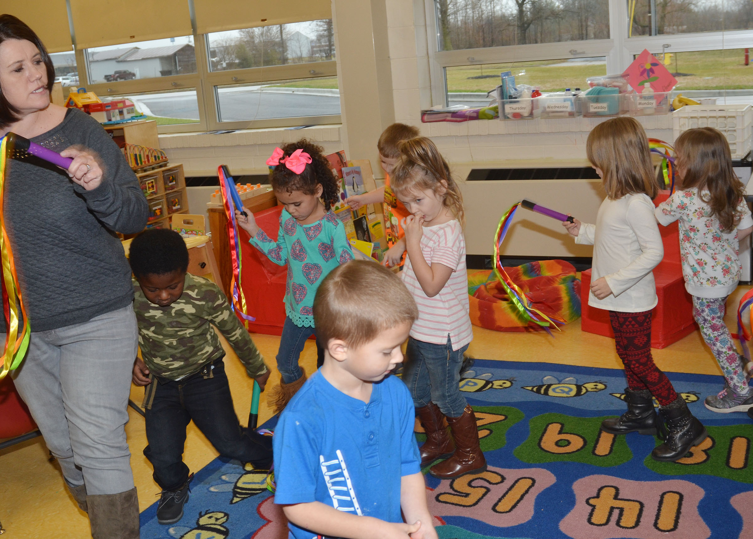 CES preschool teacher Denise Spencer leads her students around the room as they dance together.