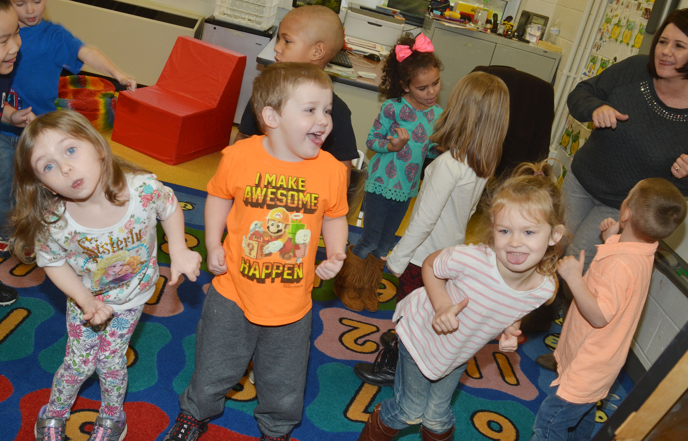 CES preschool students, from left Dahlia Ward, Levi Dye and Lilly Spencer stick their tongues out as they dance.