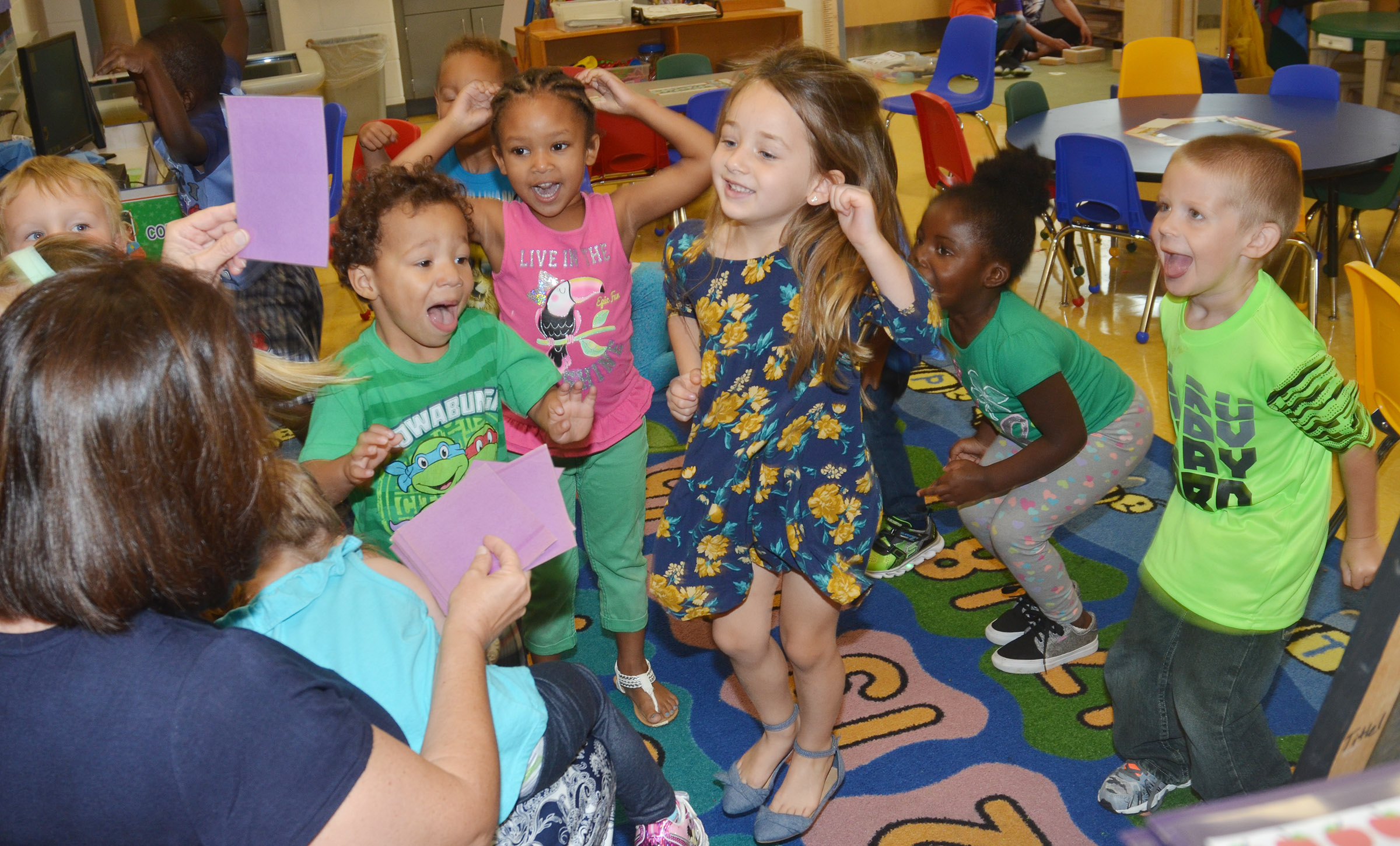 CES preschool students have fun while following teacher Denise Spencer's directions.