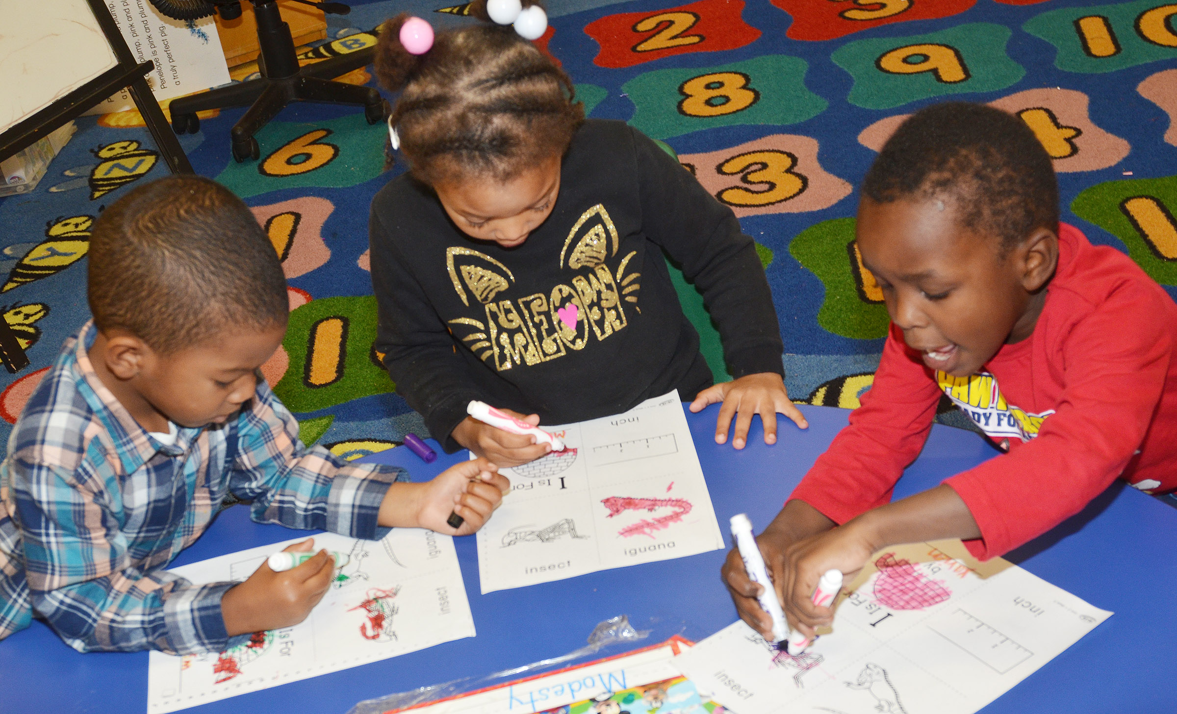 From left, CES preschool students Rakim Dunn, Modesty Taylor and Xavien Smith color their worksheets containing words that start with I.