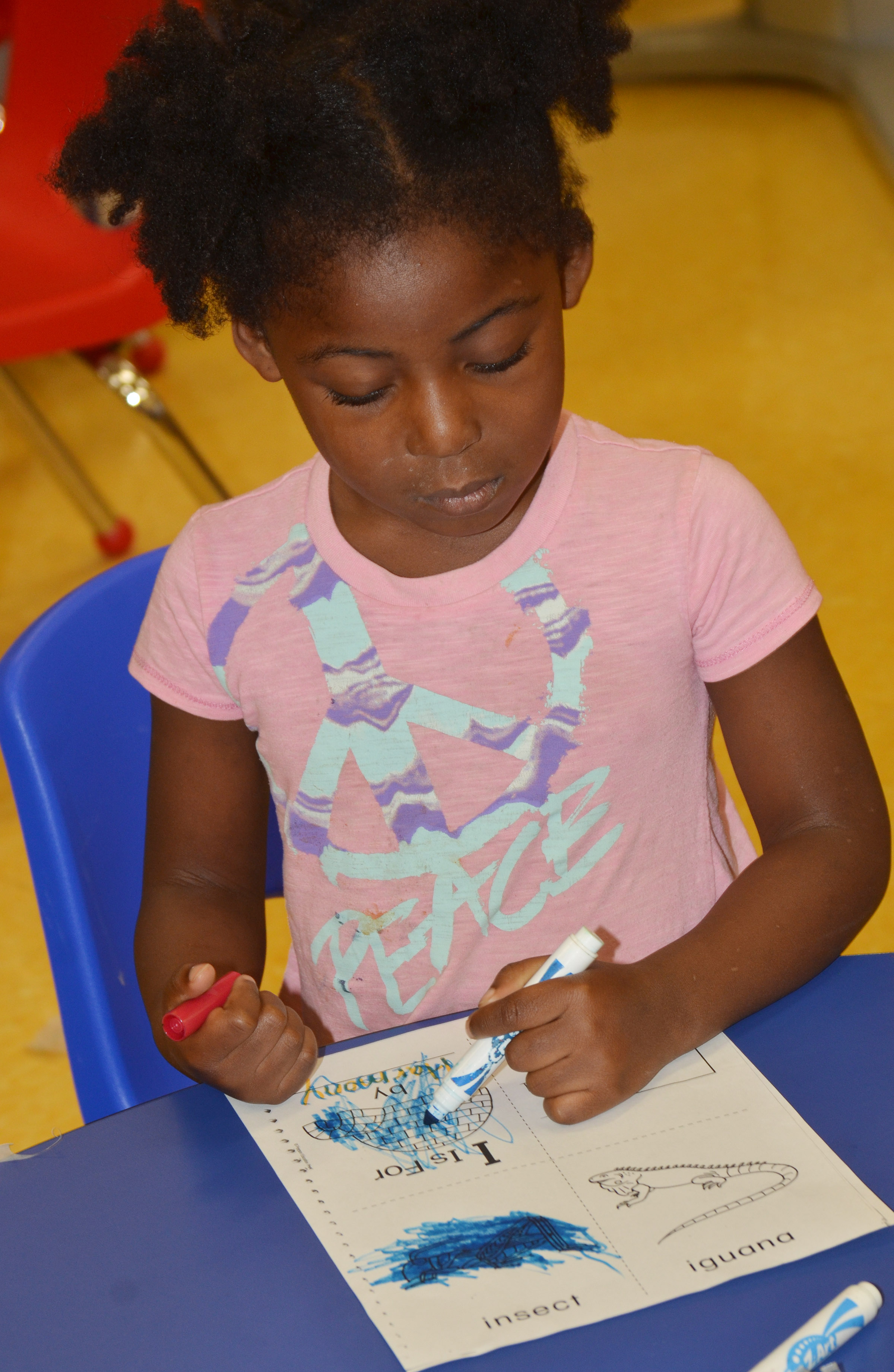 CES preschool student Harmony Brown colors her worksheet containing words that start with I.