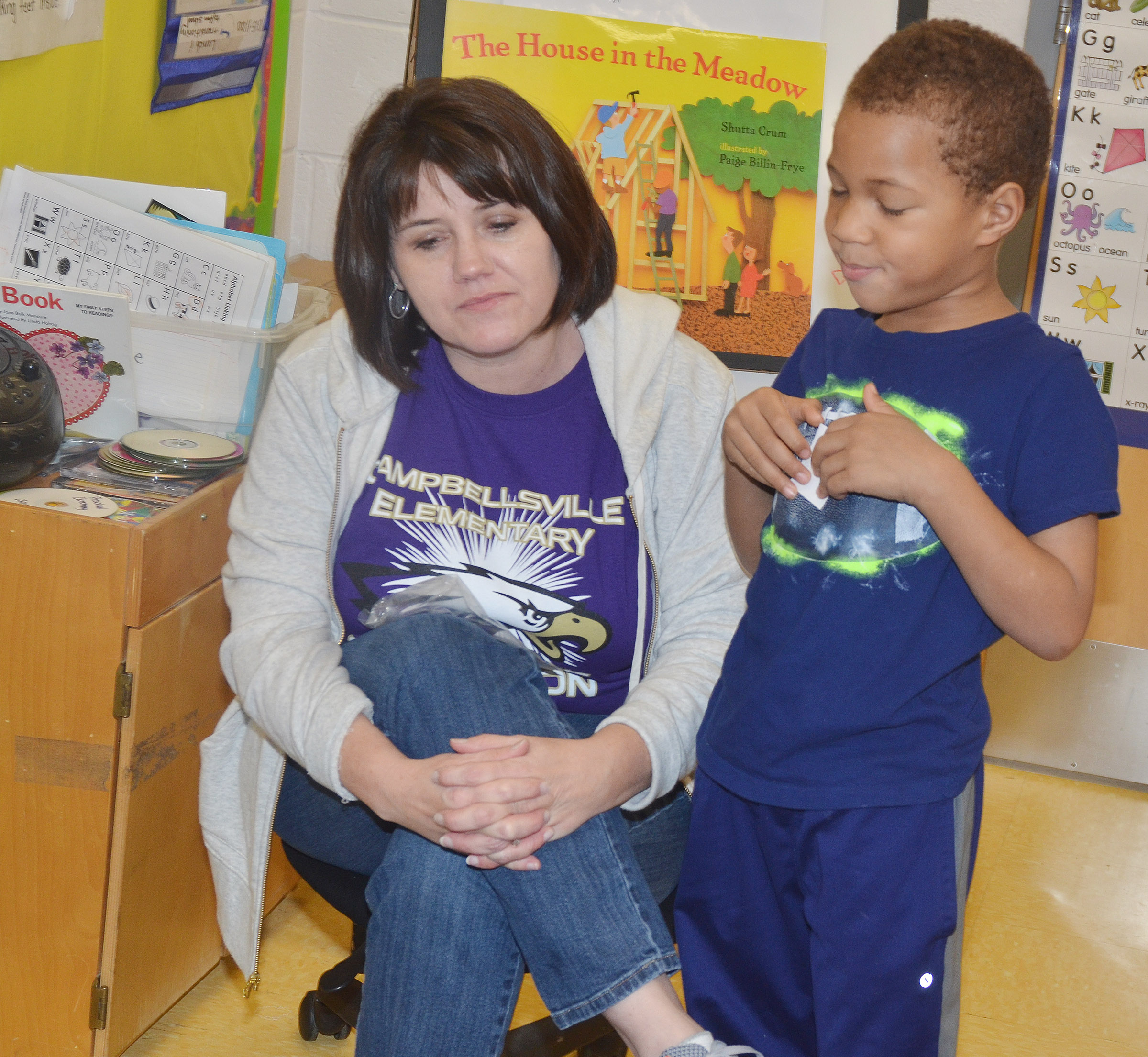 CES preschool teacher Denise Spencer asks Jamerius Miller to give his classmates clues about a word that starts with the letter V.