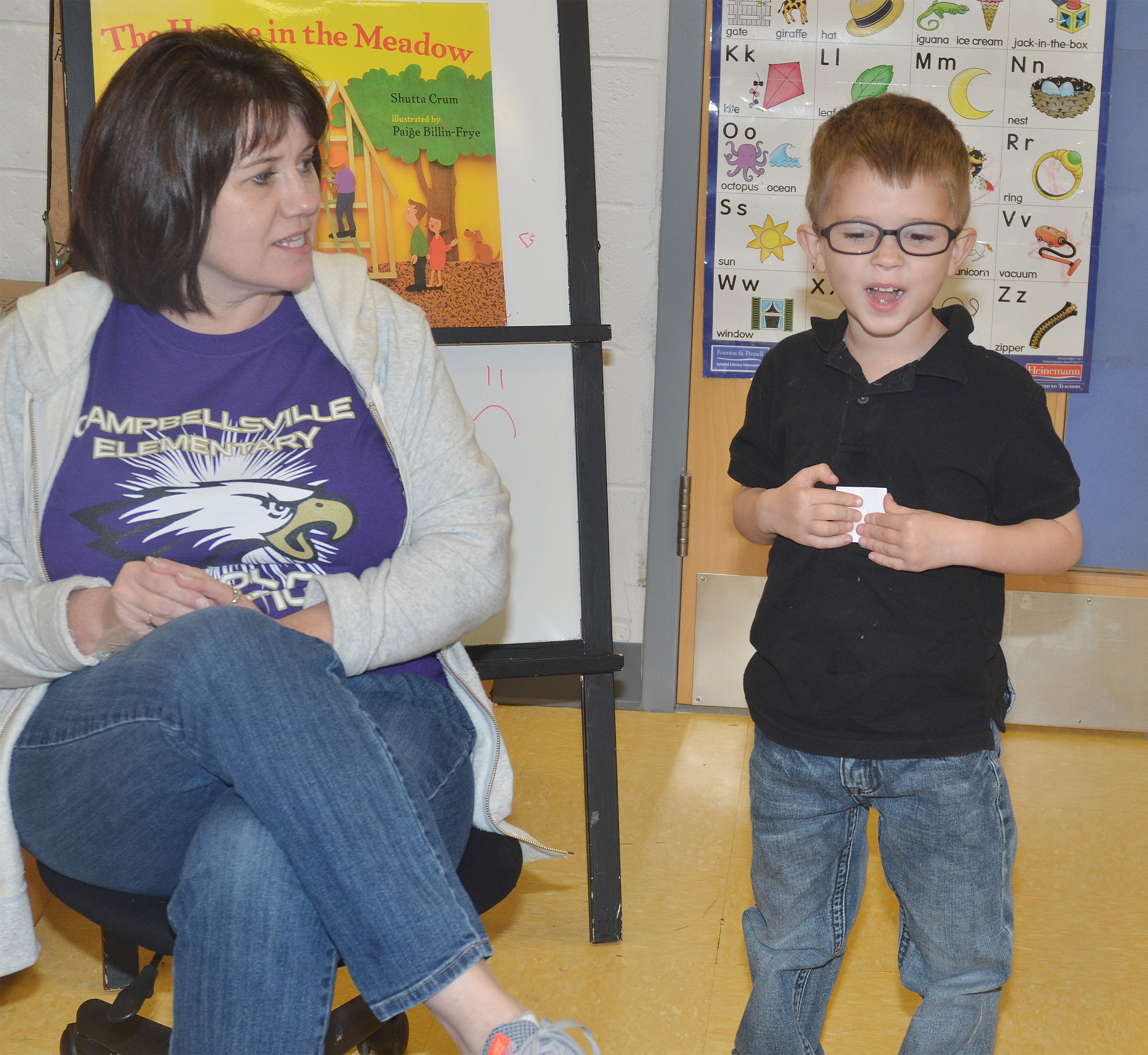 CES preschool teacher Denise Spencer asks Andrew Stout to give his classmates clues about a word that starts with the letter V.