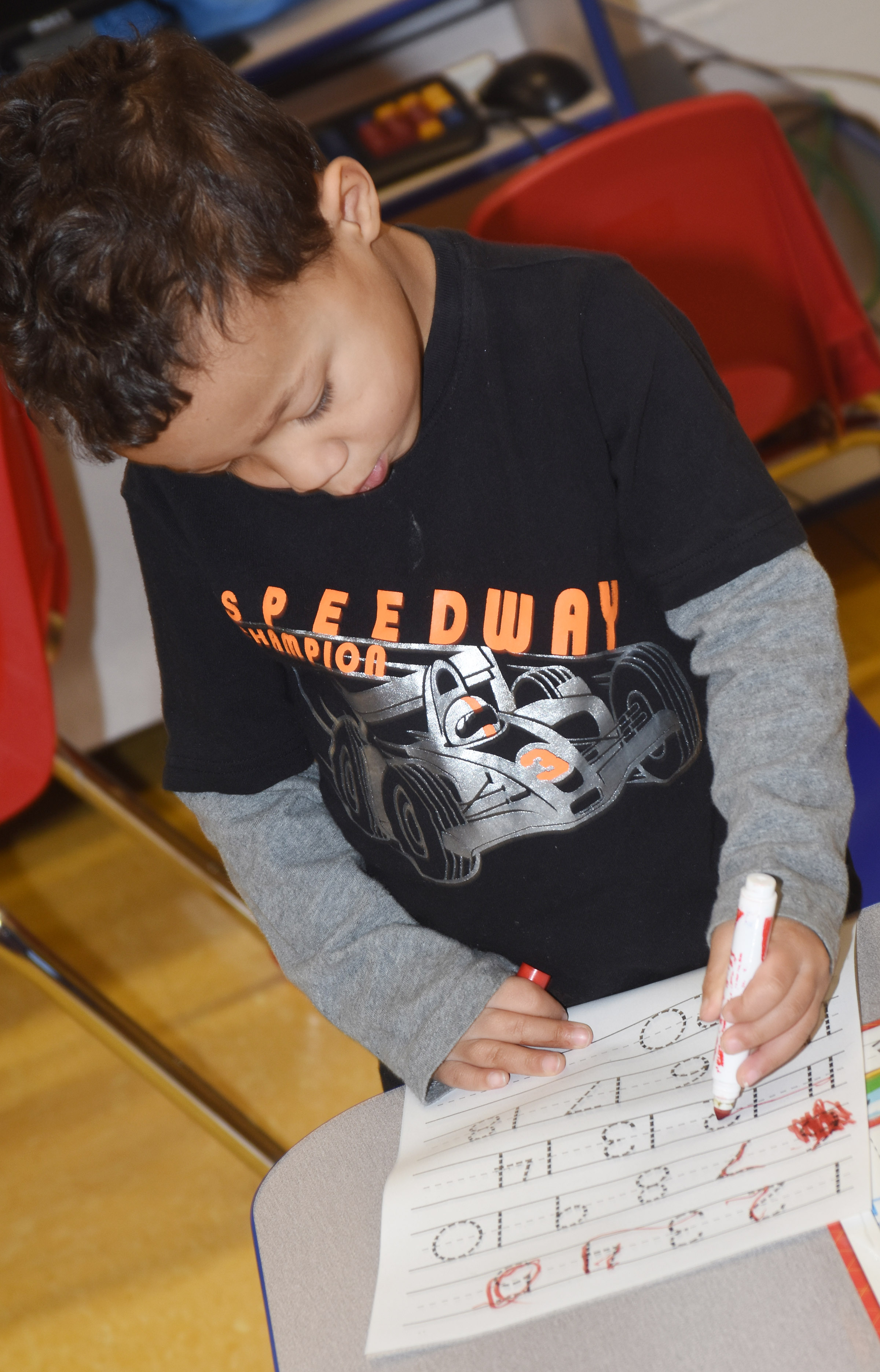 CES preschool student Ace Turner writes the number 12.