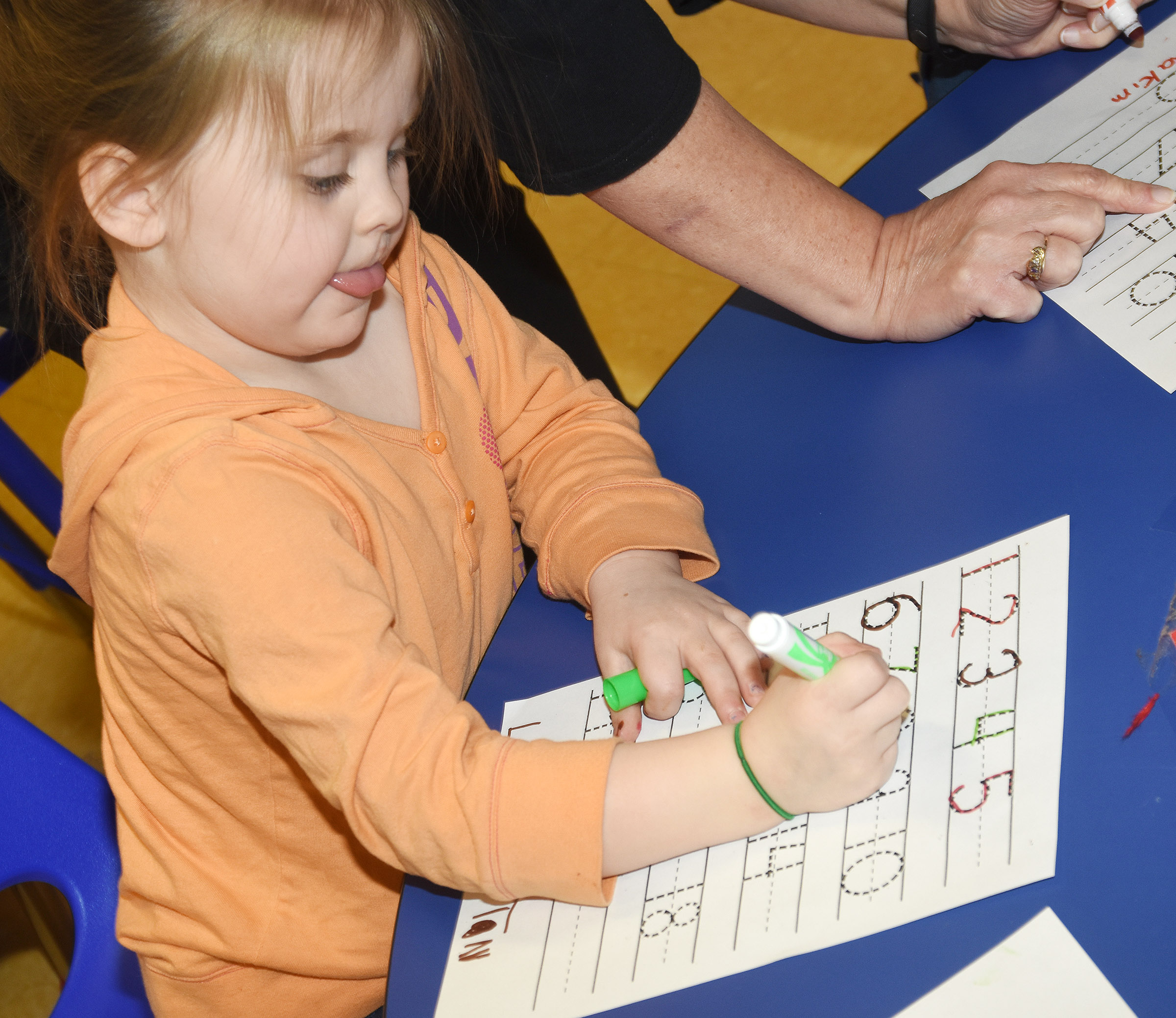 CES preschool student Tori Clark writes the number eight.