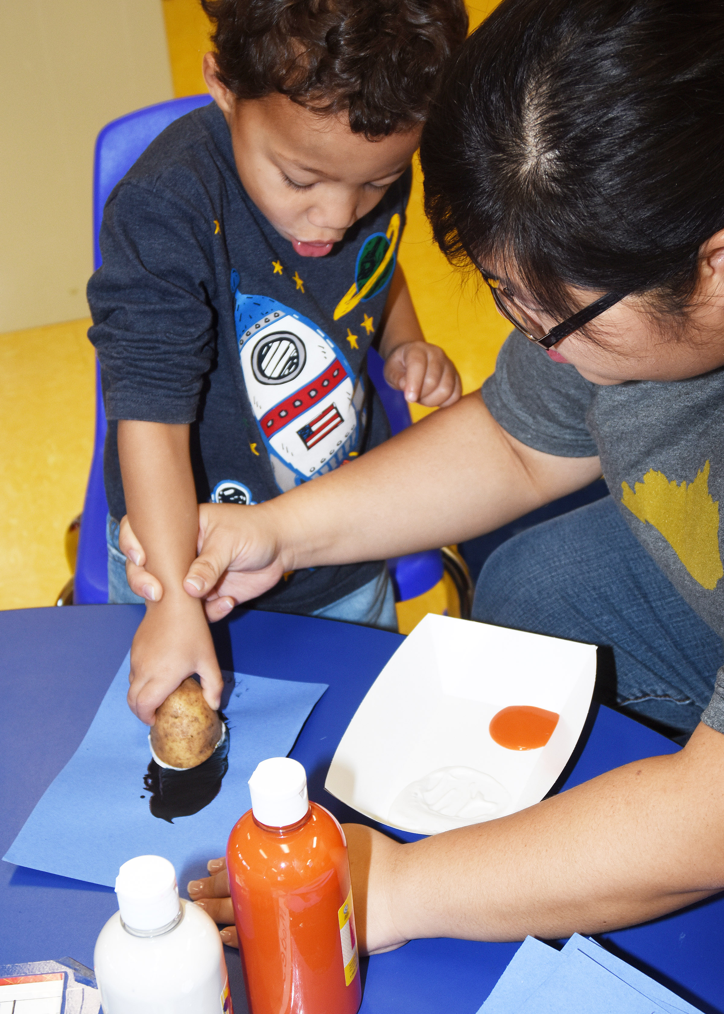 CES Preschool Assistant Brittany Johnson helps Ace Turner paint his penguin.
