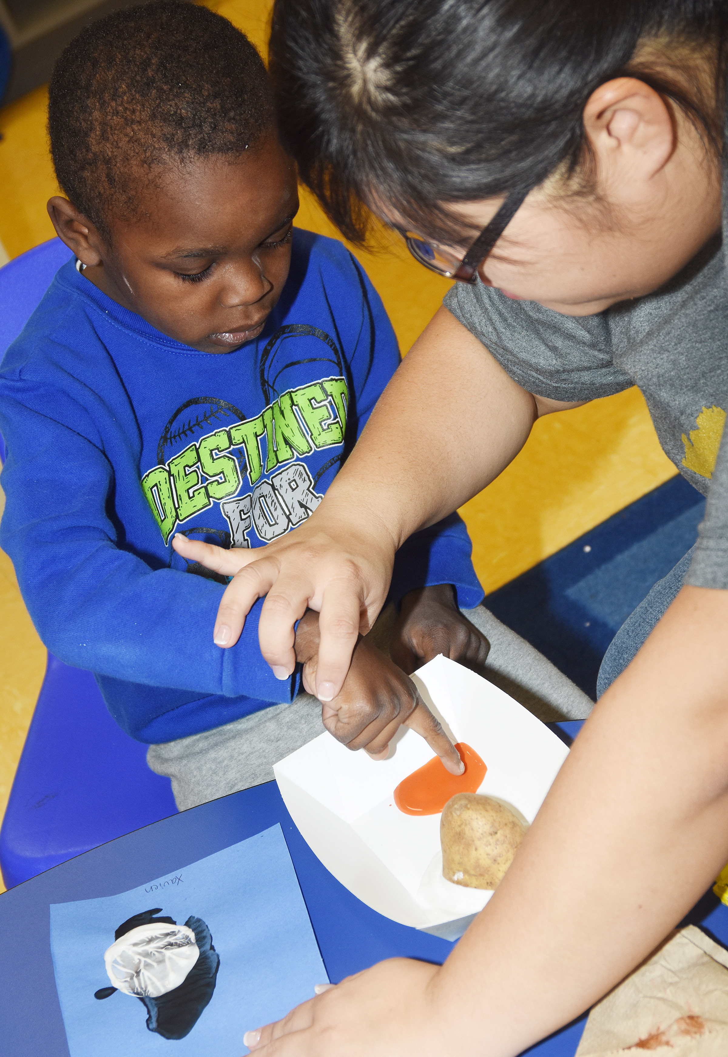 CES Preschool Assistant Brittany Johnson helps Xavien Smith paint his penguin.