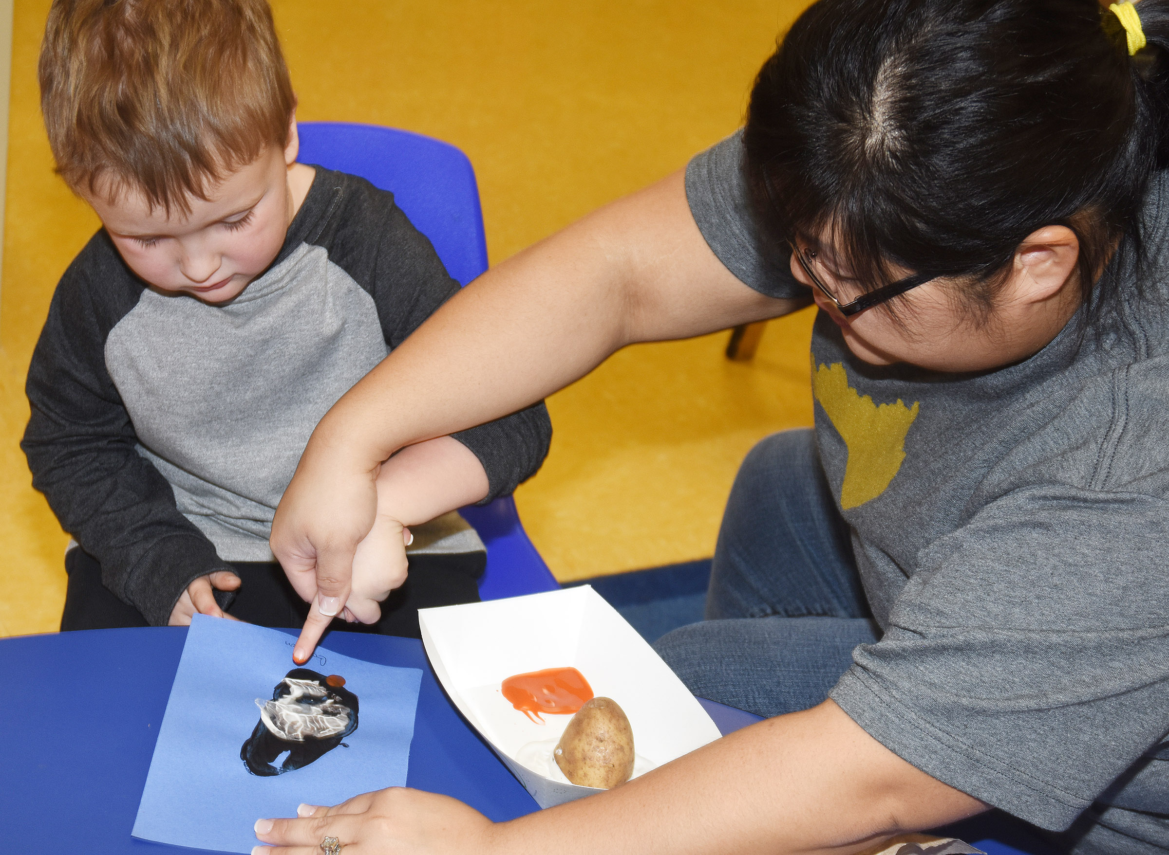CES Preschool Assistant Brittany Johnson helps Gannon Scott add feet to his penguin.