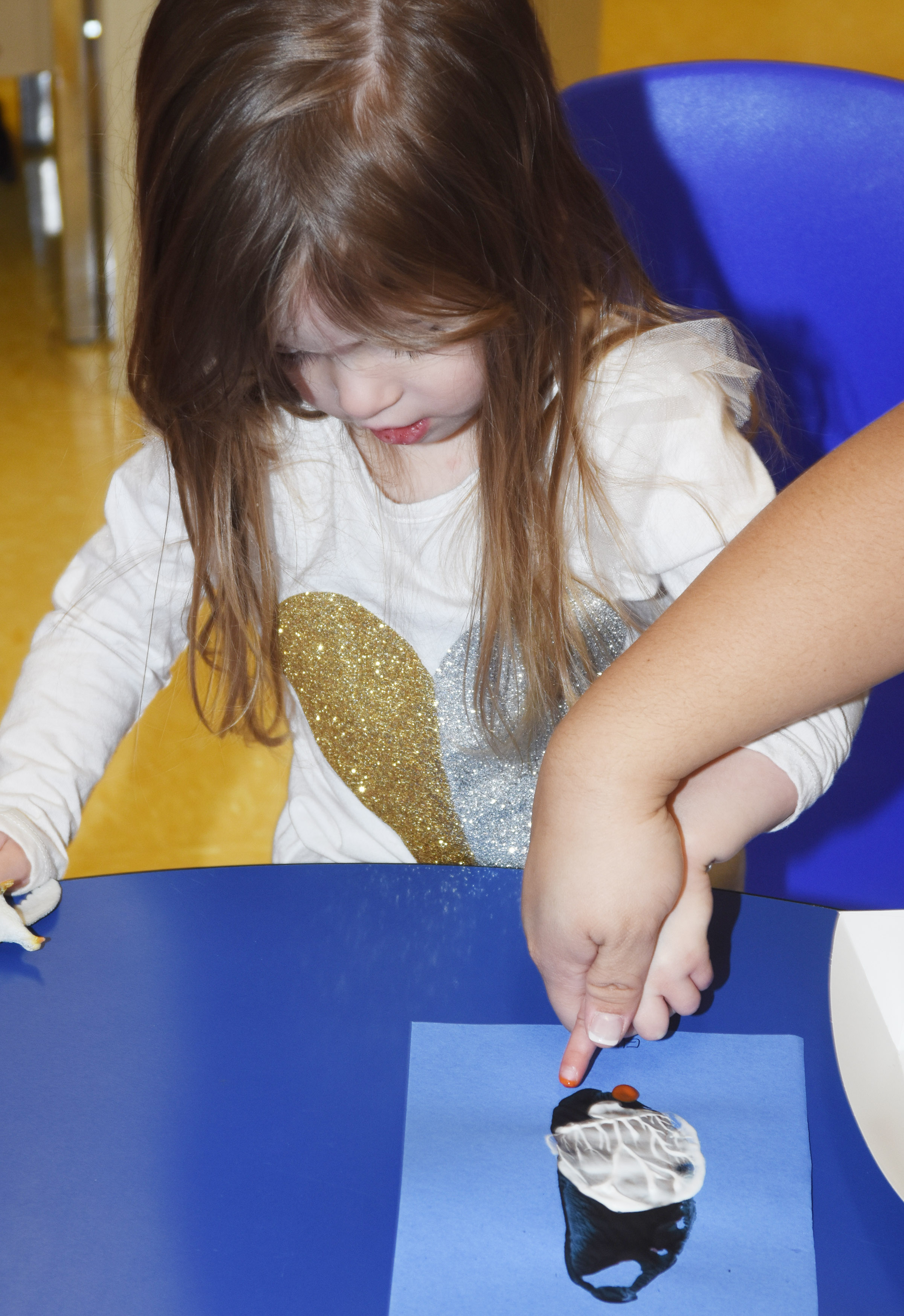 CES preschool student Ella Woodbury adds feet to her penguin.