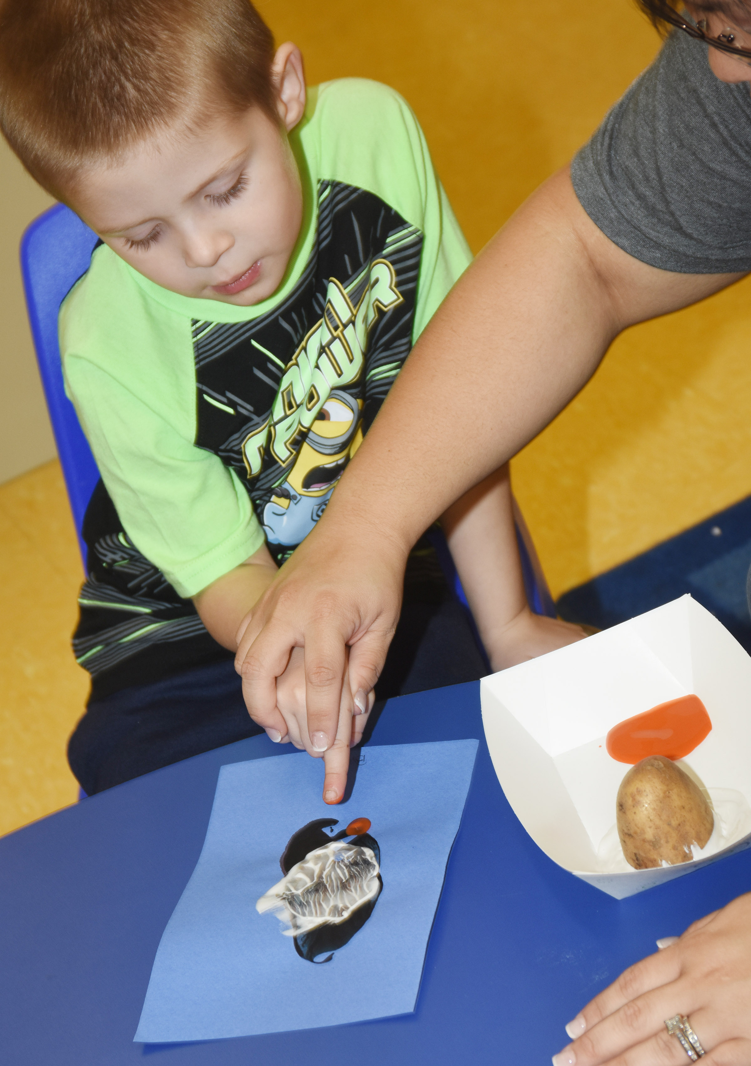 CES Preschool Assistant Brittany Johnson helps Brian Daniels add feet to his penguin.