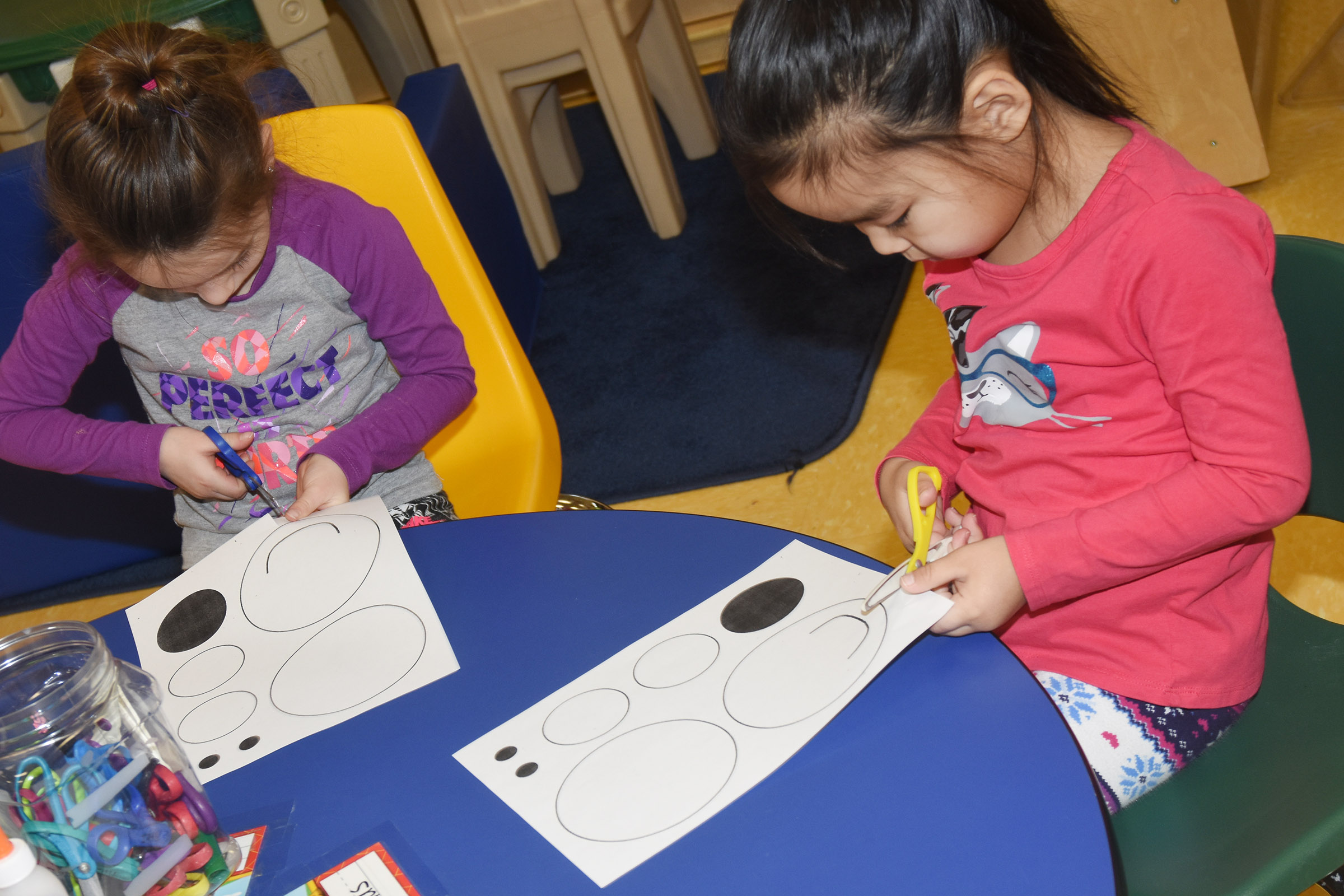 CES preschool students Lylah Davis, at left, and Marla Bat cut out the shapes to make their polar bears.