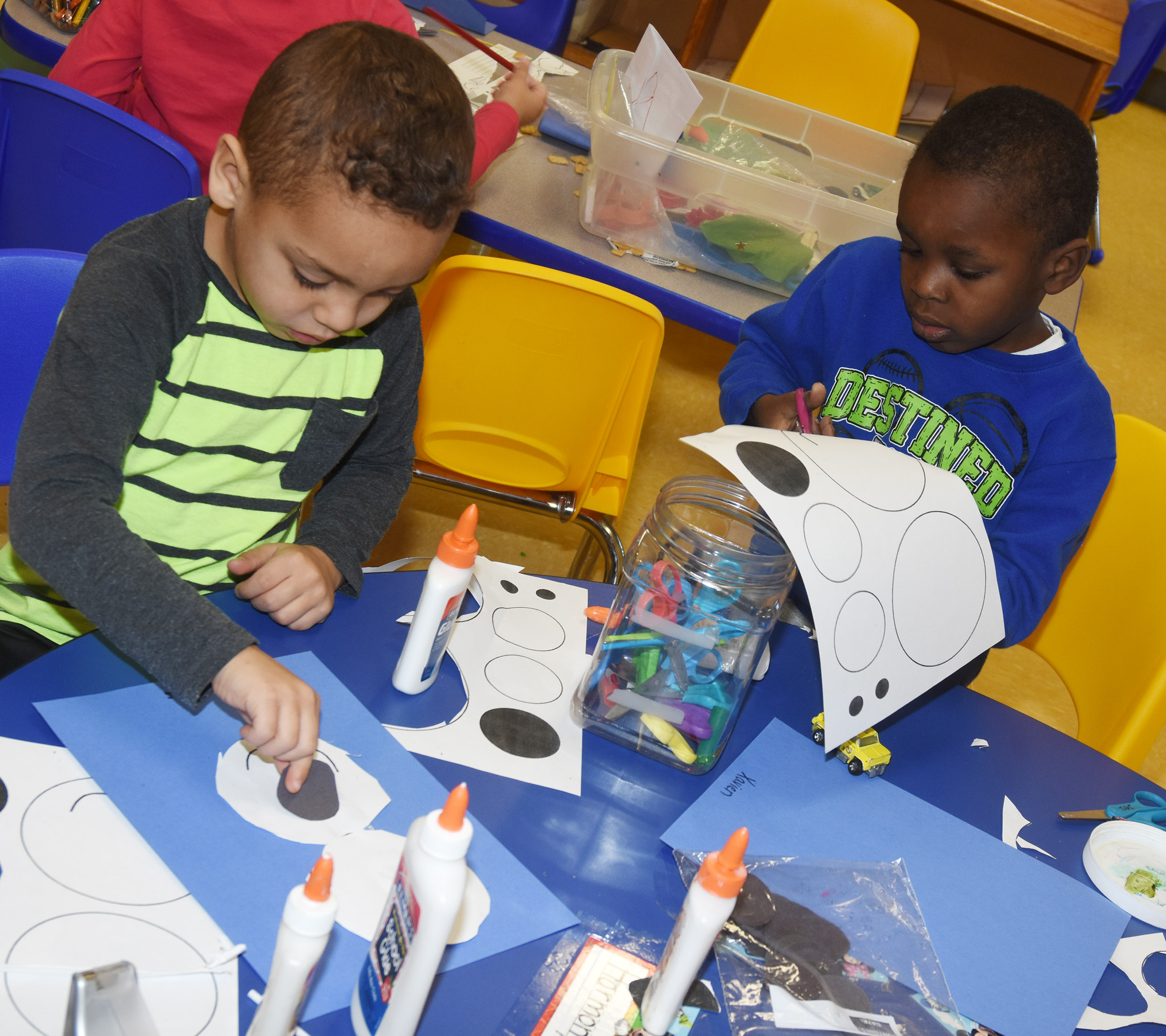 CES preschool students Jasiahas Anderson, at left, and Xavien Smith make their polar bears.