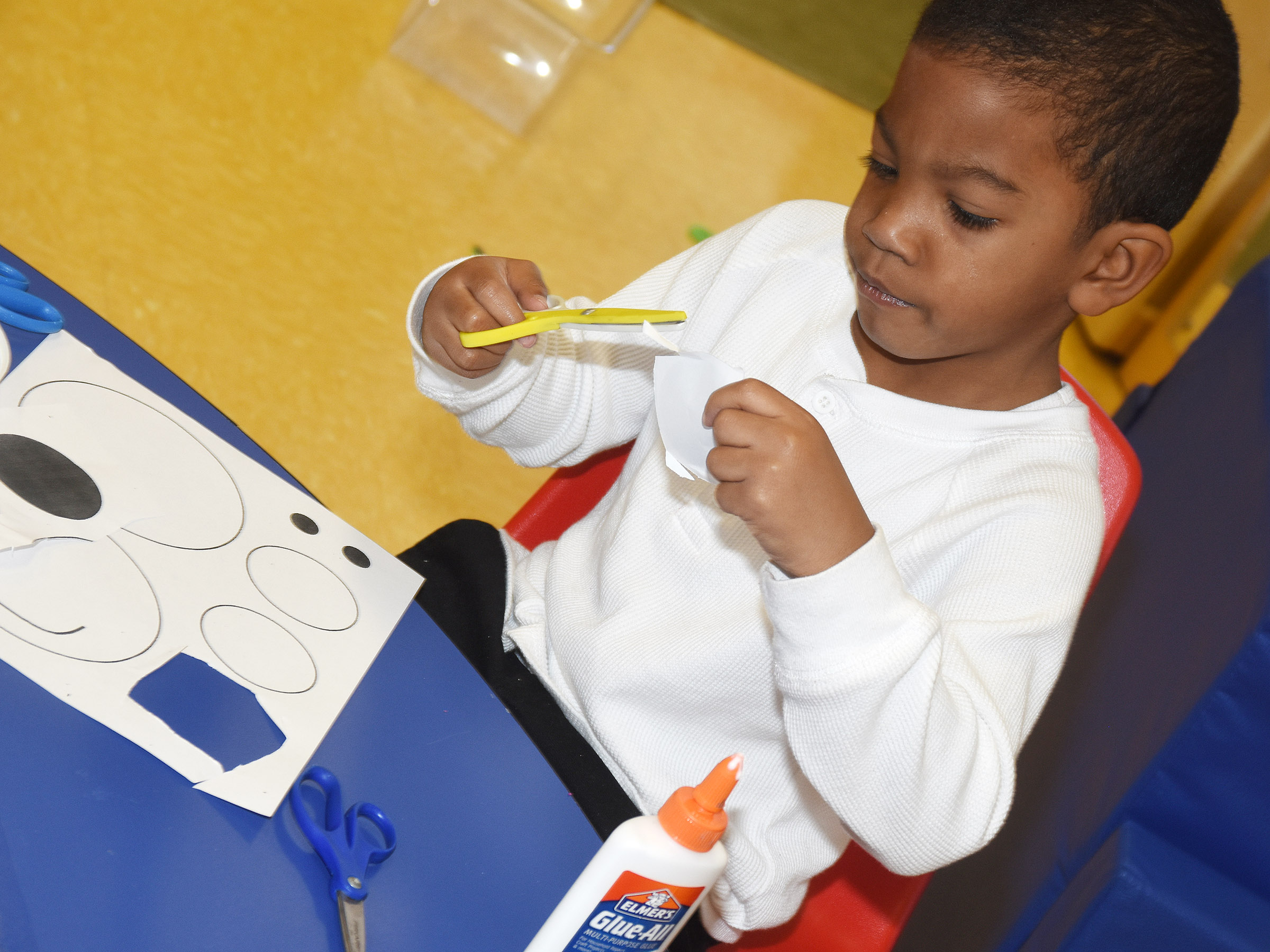 CES preschool student Rakim Dunn cuts out the shapes to make his polar bear.