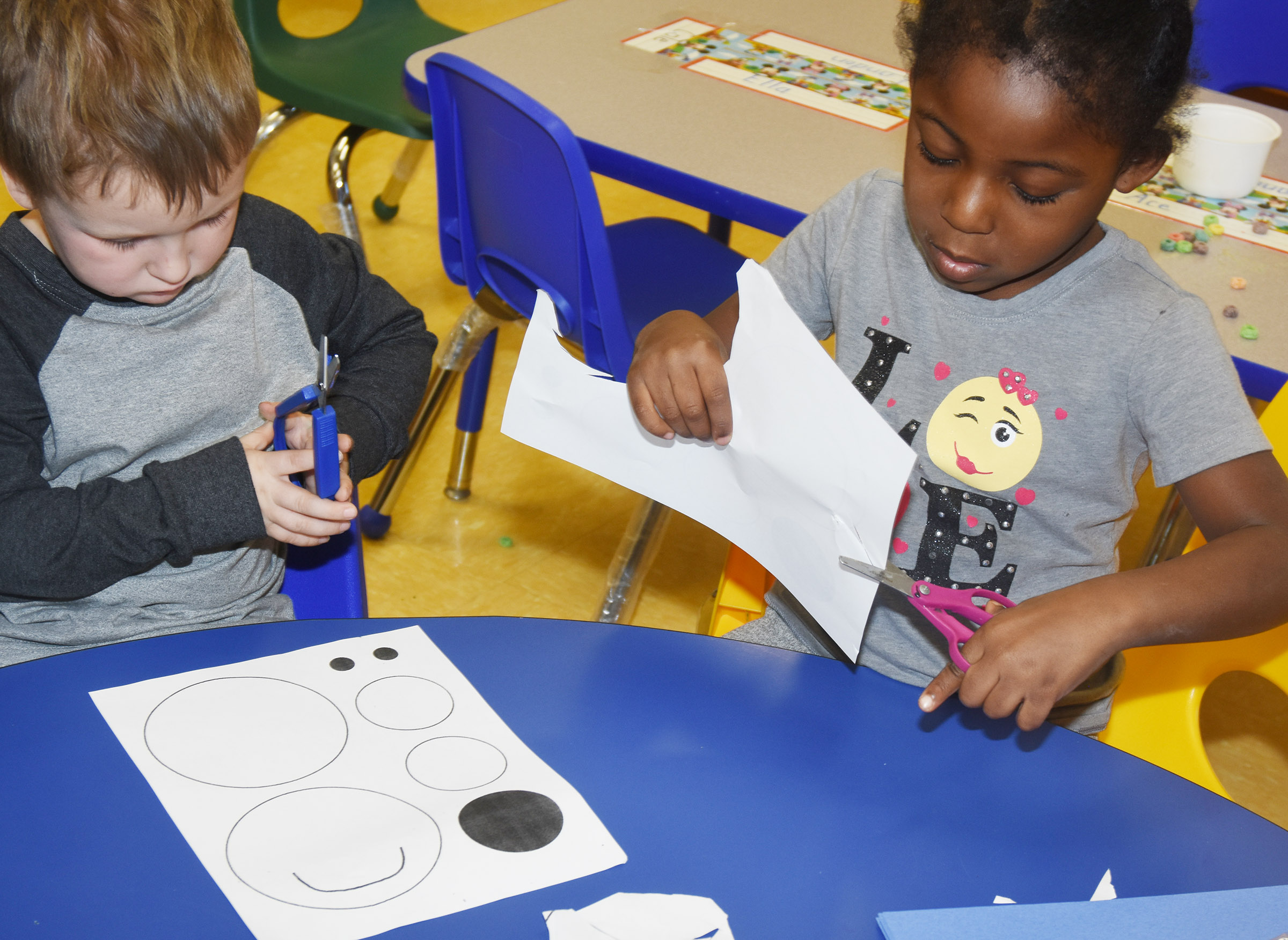 CES preschool students Gannon Scott, at left, and Harmony Brown cut out the shapes to make their polar bears.
