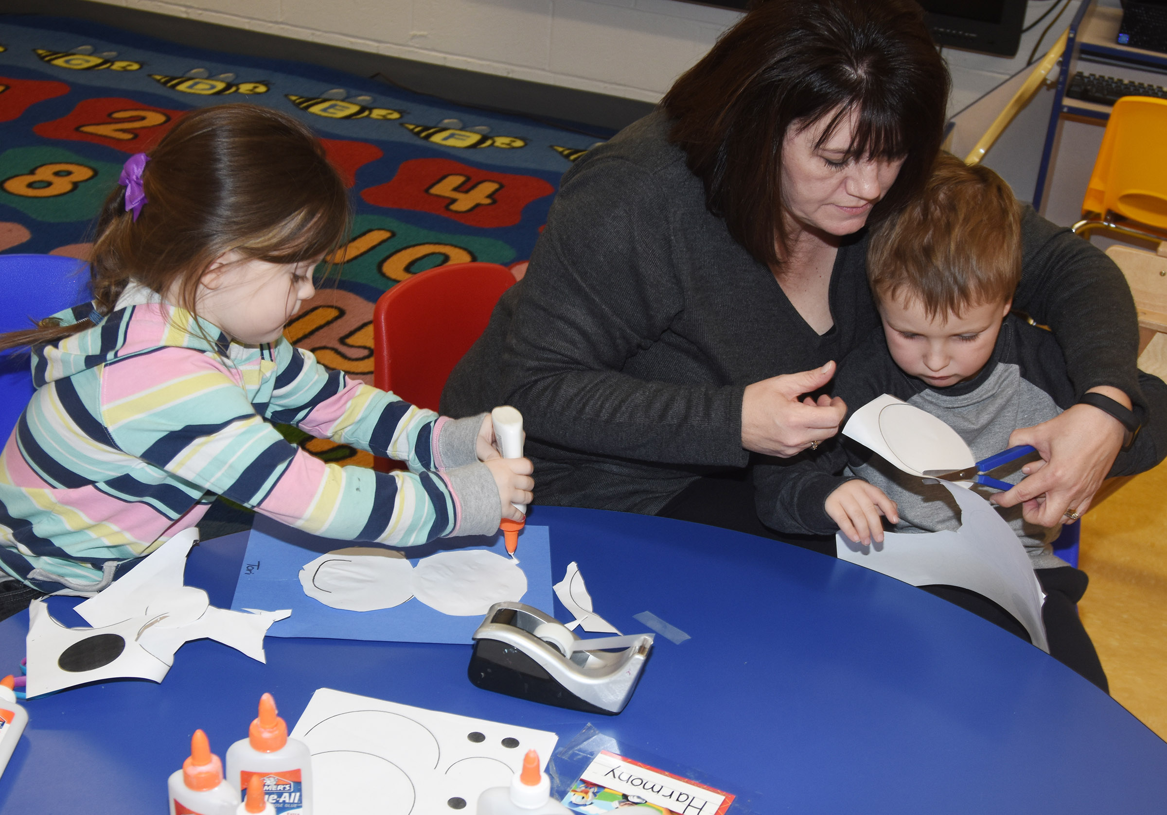 CES preschool teacher Denise Spencer helps Gannon Scott cut out the shapes to make his polar bear as Tori Clark glues hers together.