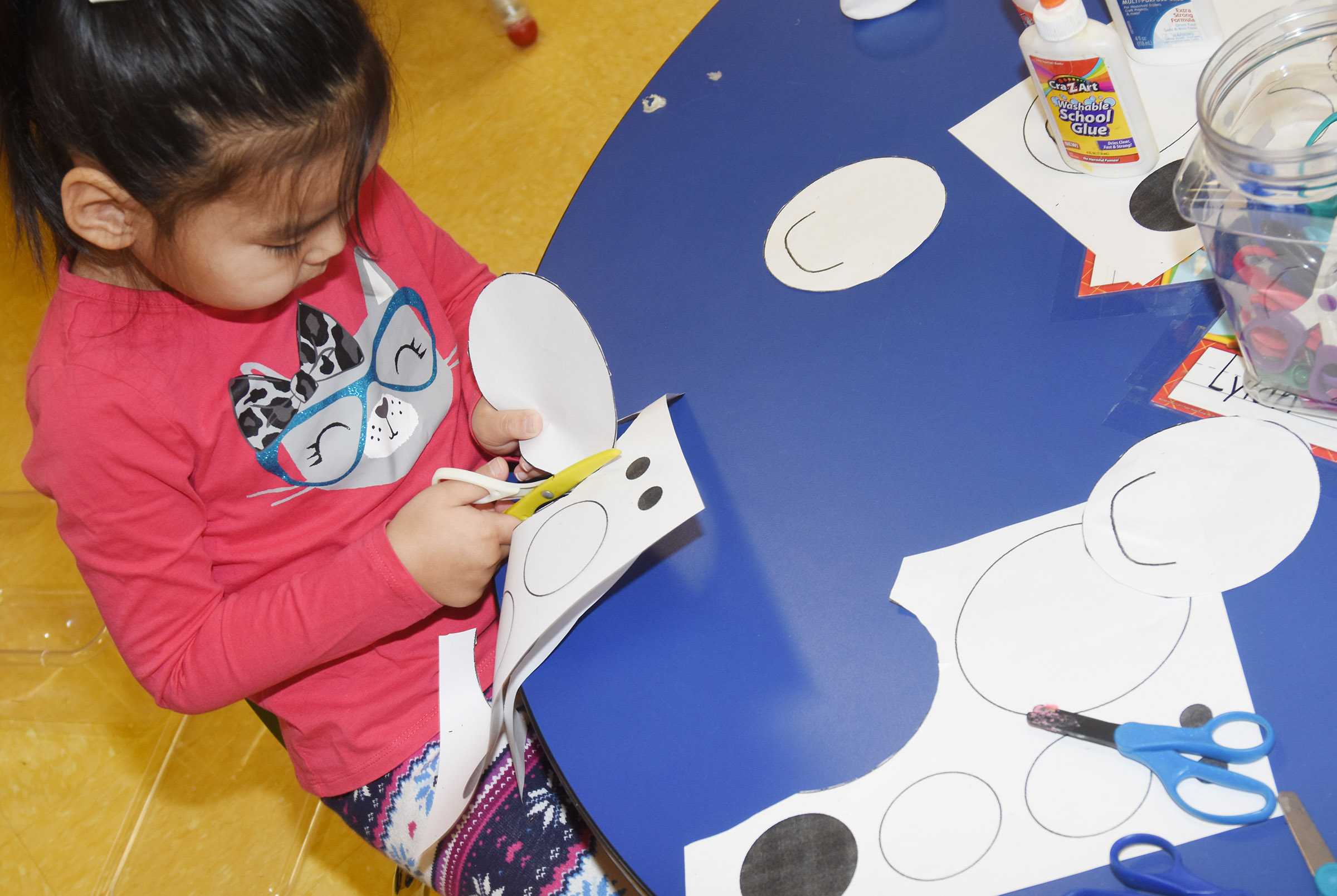 CES preschool student Marla Bat cuts out the shapes to make her polar bear.