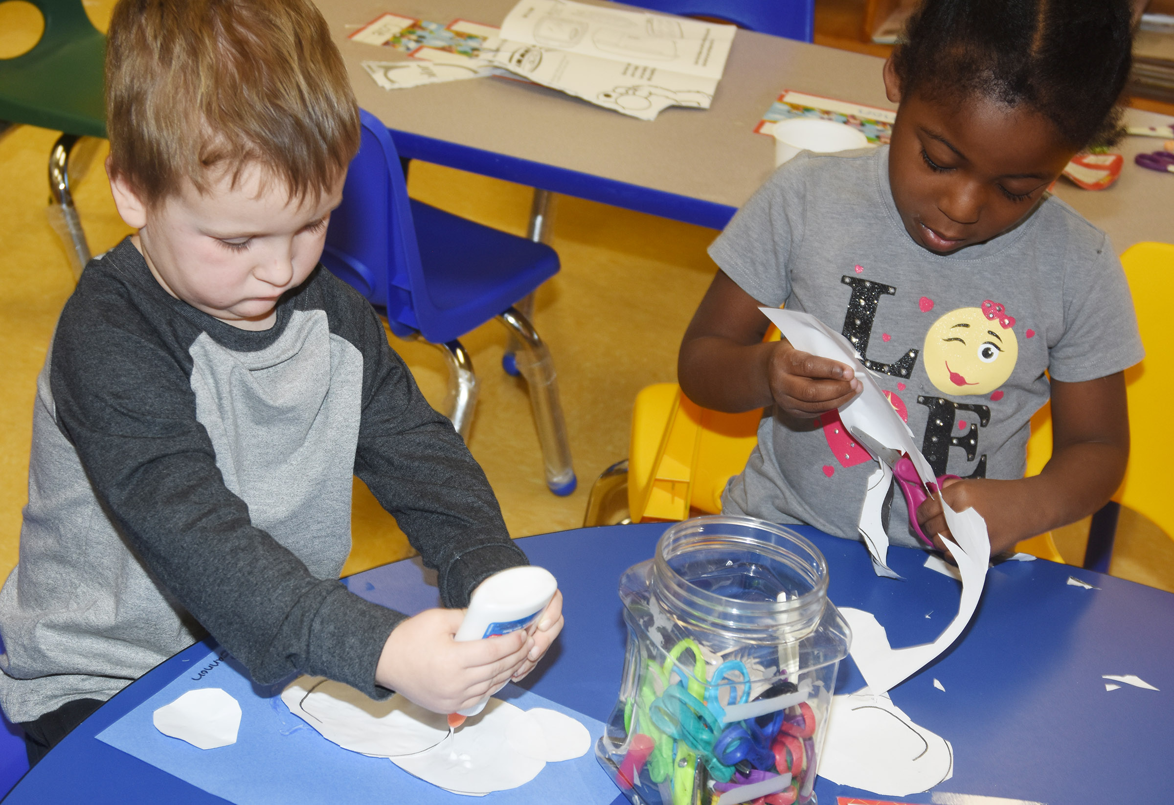 CES preschool students Gannon Scott, at left, and Harmony Brown make their polar bears.