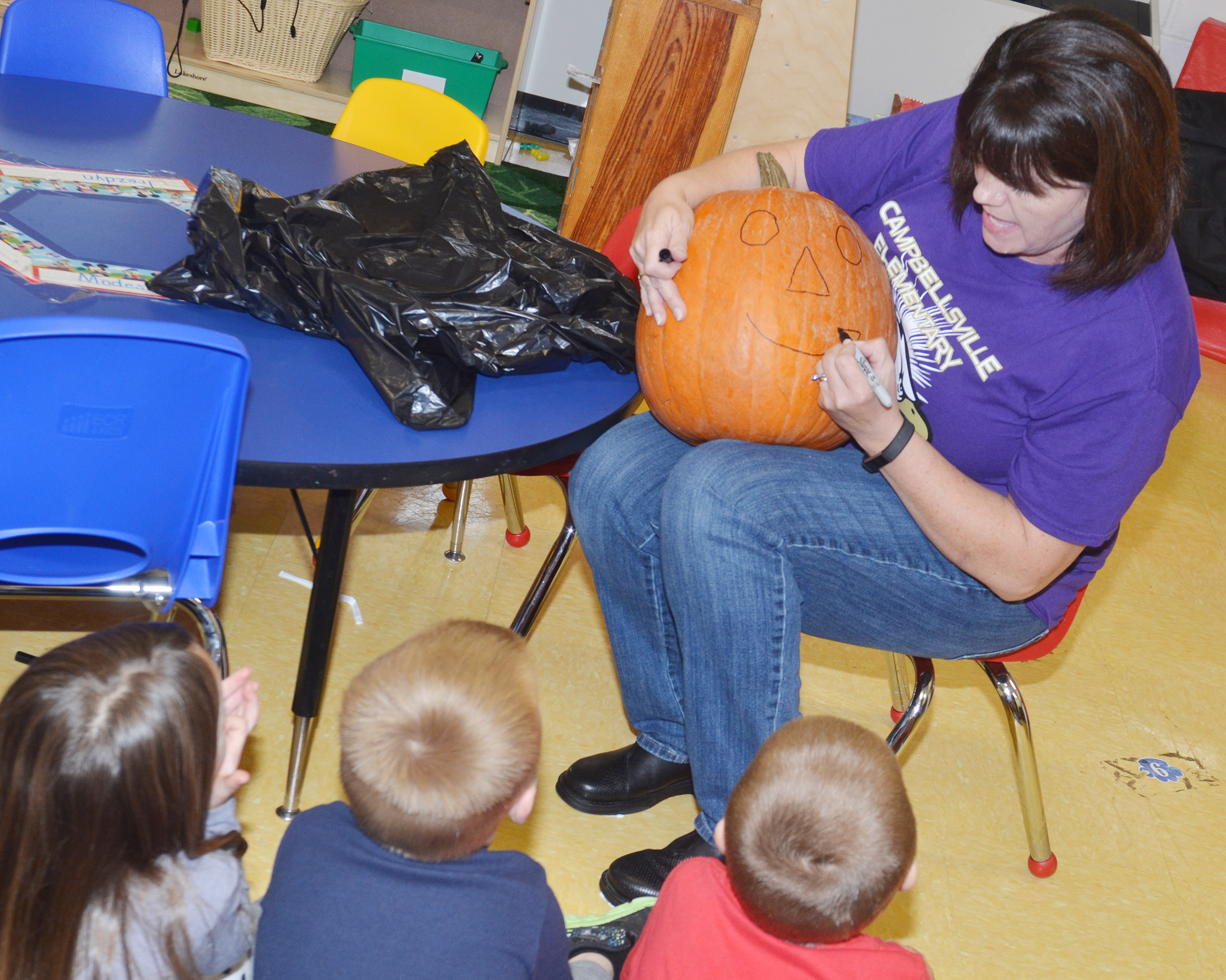 CES preschool teacher Denise Spencer draws a face on her class's pumpkin.