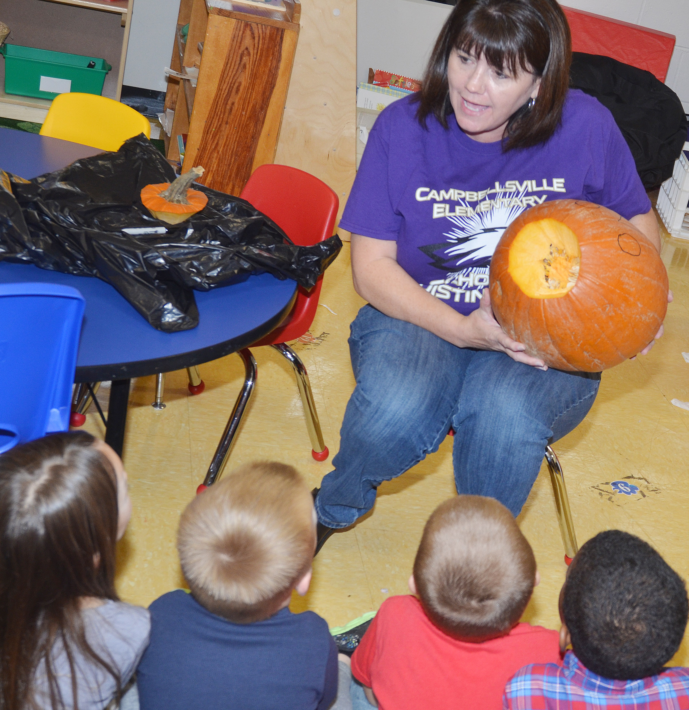 CES preschool teacher Denise Spencer shows her students the inside of their pumpkin.