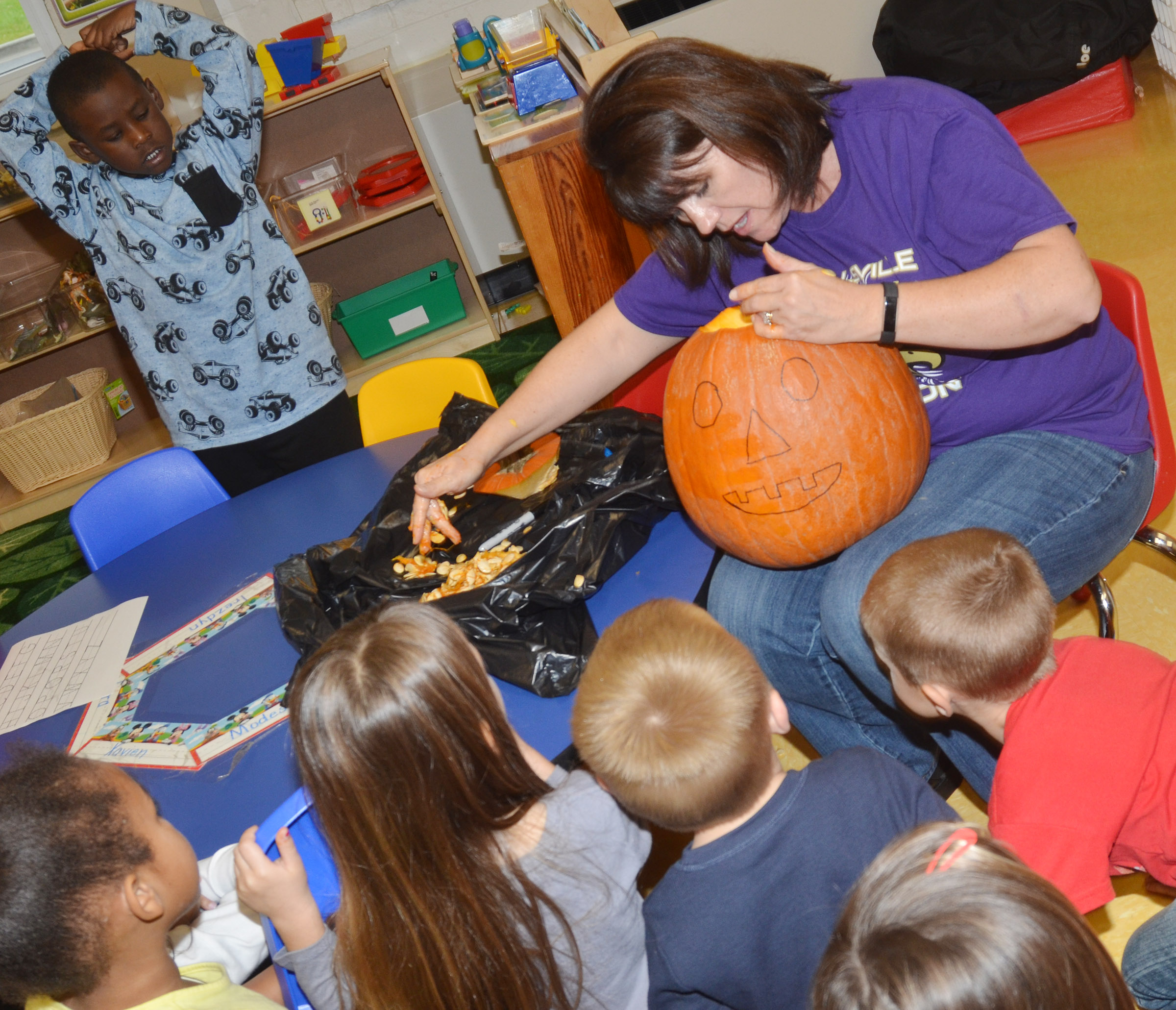 CES preschool teacher Denise Spencer removes the seeds from the class's pumpkin.