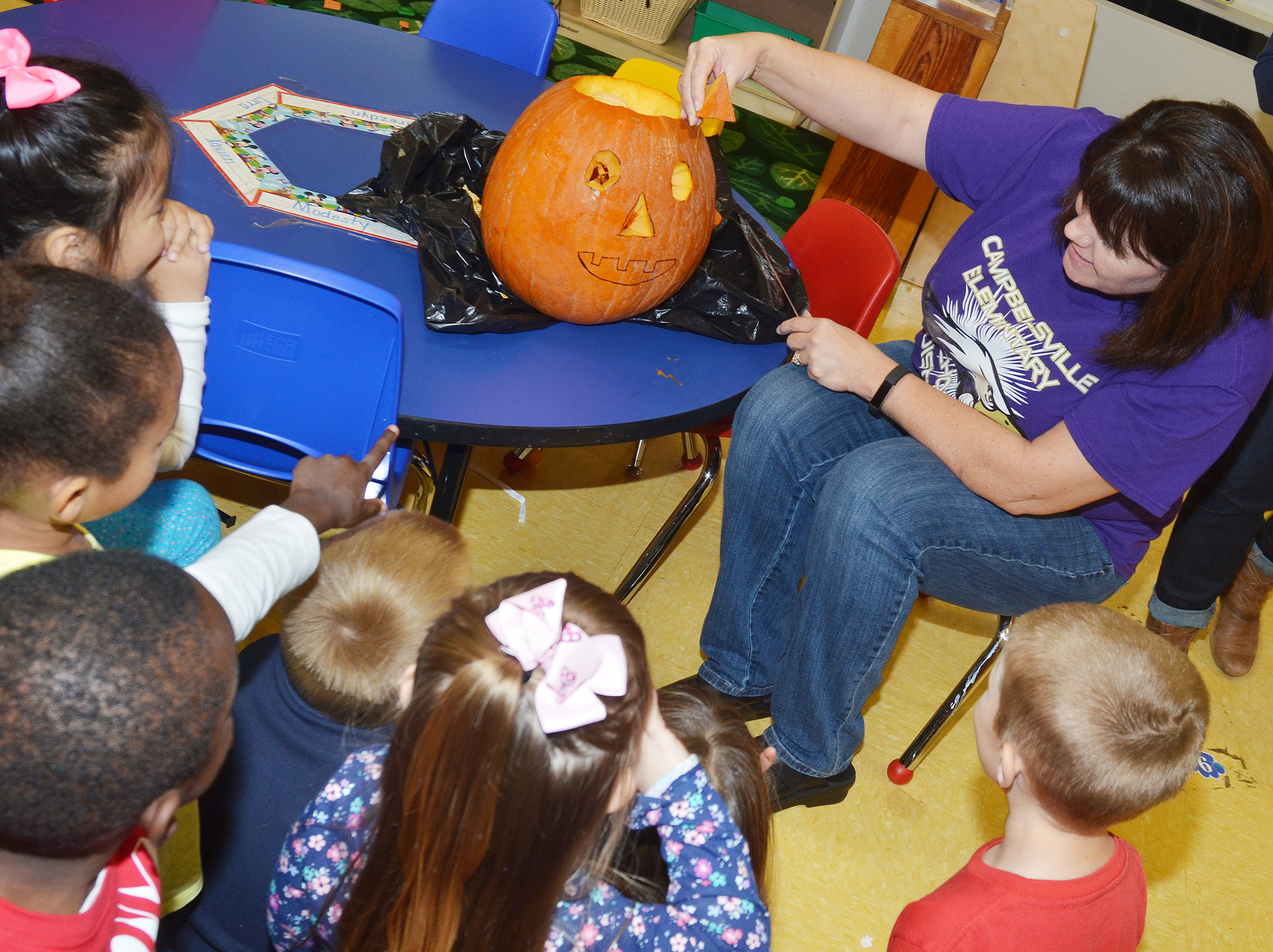 CES preschool teacher Denise Spencer carves her class's pumpkin.