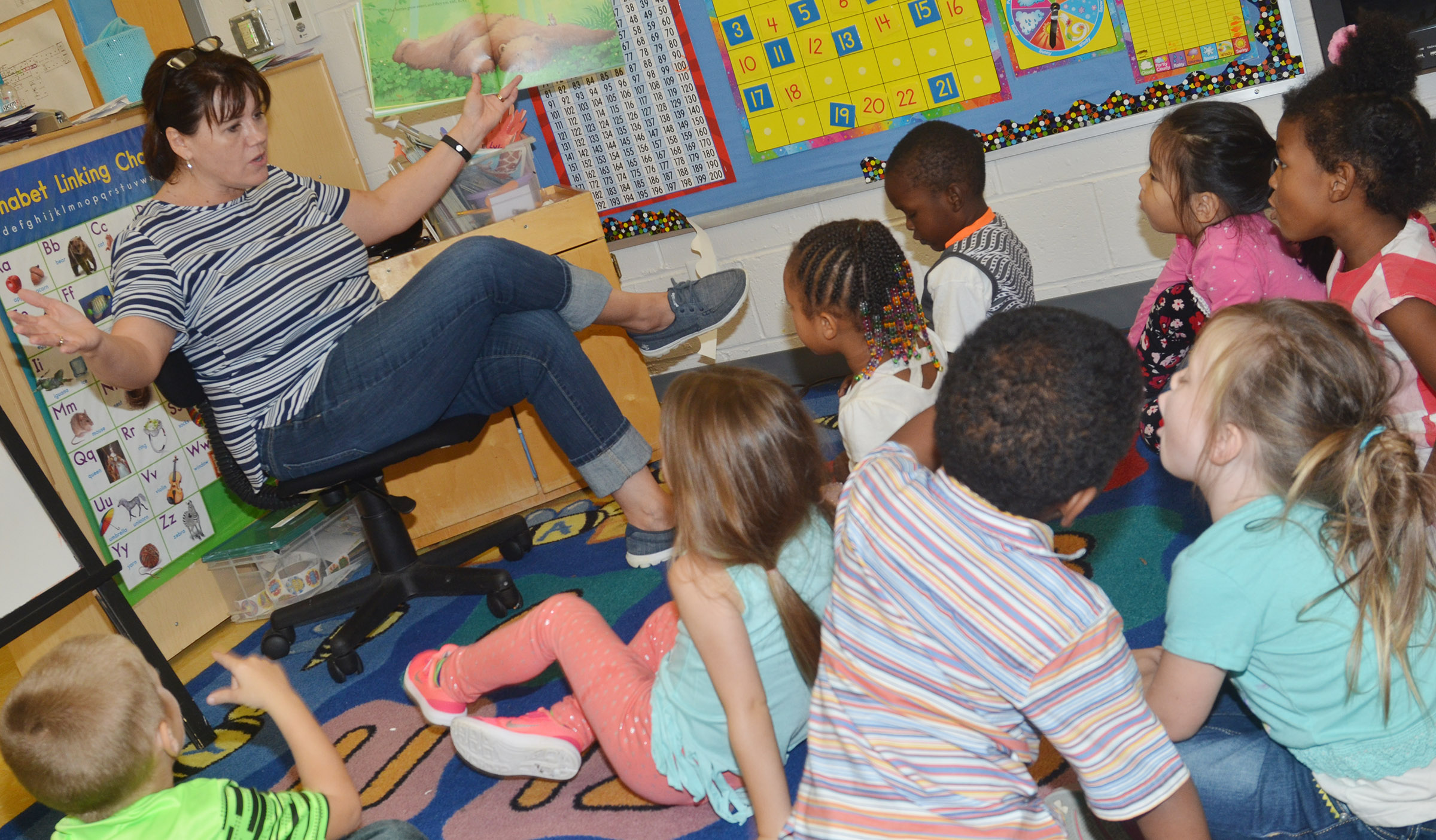 CES preschool teacher Denise Spencer reads a book about a bear to her students.