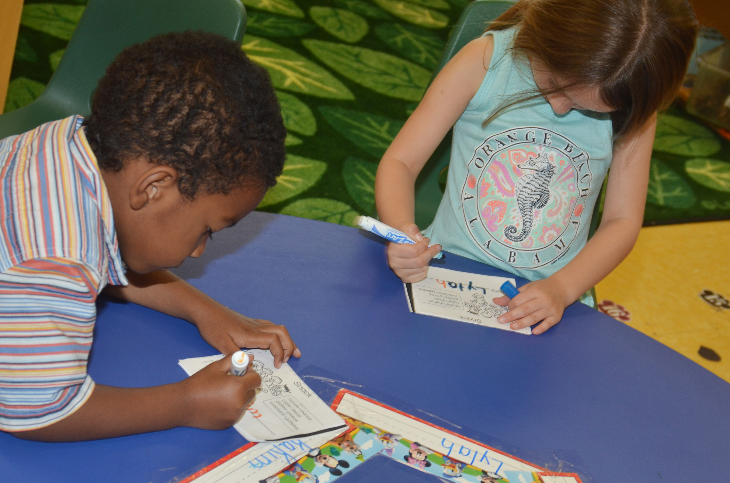 CES preschool students Rakim Dunn, at left, and Lylah Davis practice writing their names.