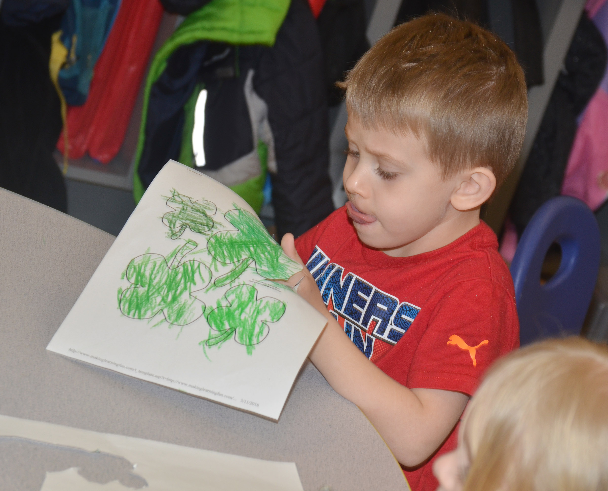 CES preschool student Elijah Russell concentrates as he cuts out his shamrocks.