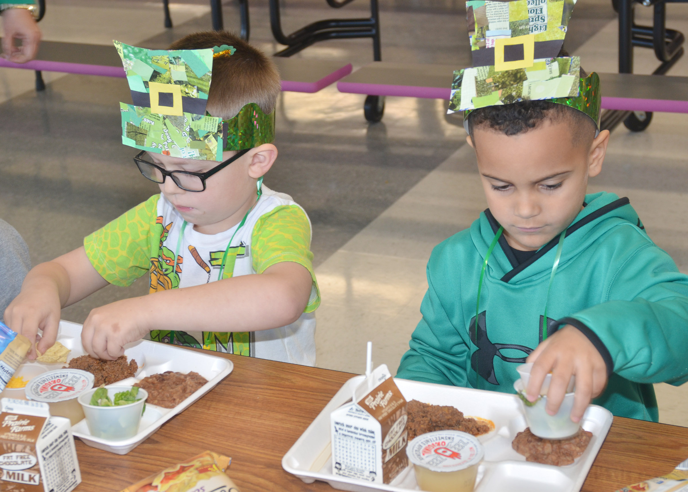 CES preschool students Reece Williams, at left, and Kingston Cowherd wear their St. Patrick's Day hats to lunch.