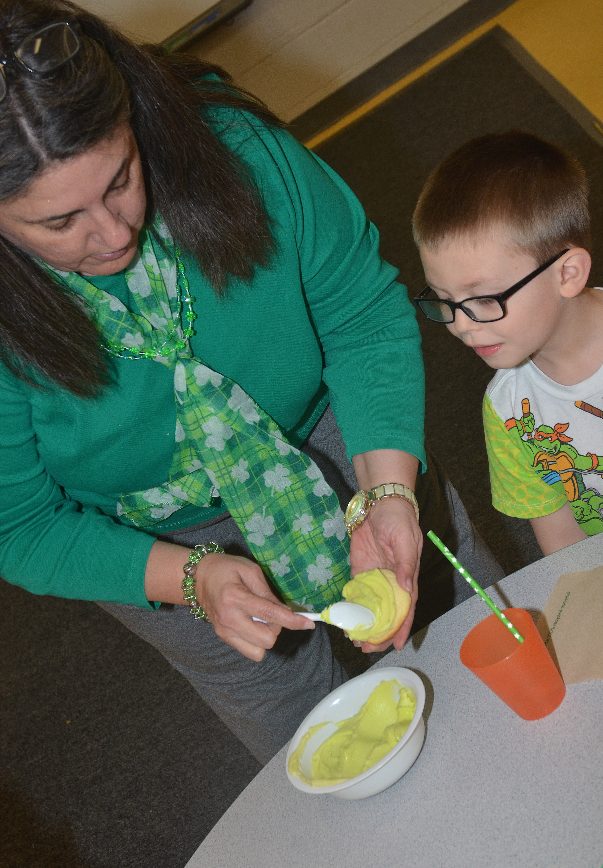 CES preschool teacher Sherry Cowherd green adds icing to Reece Williams's cookie.
