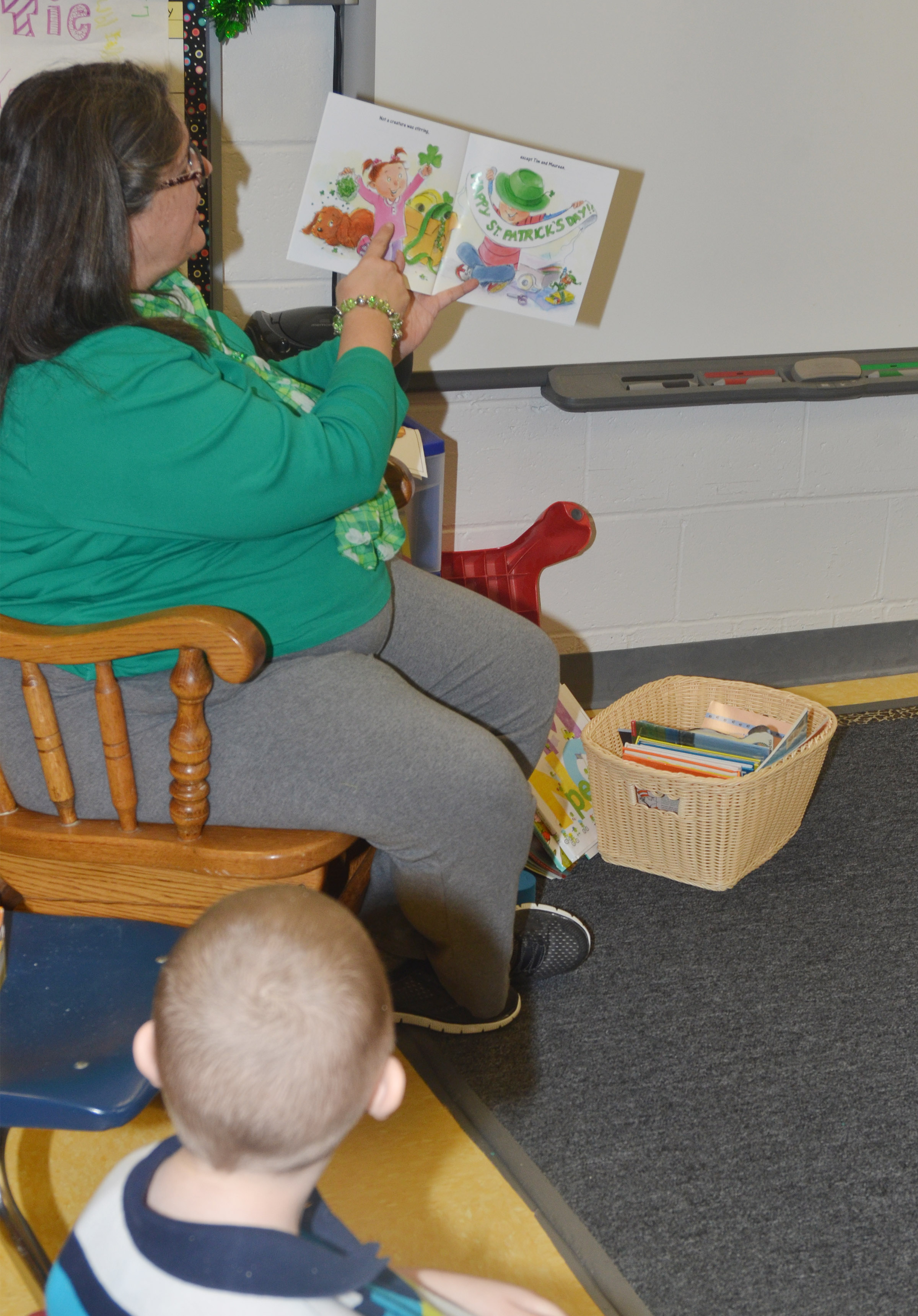 CES preschool teacher Sherry Cowherd reads to her students about St. Patrick's Day.