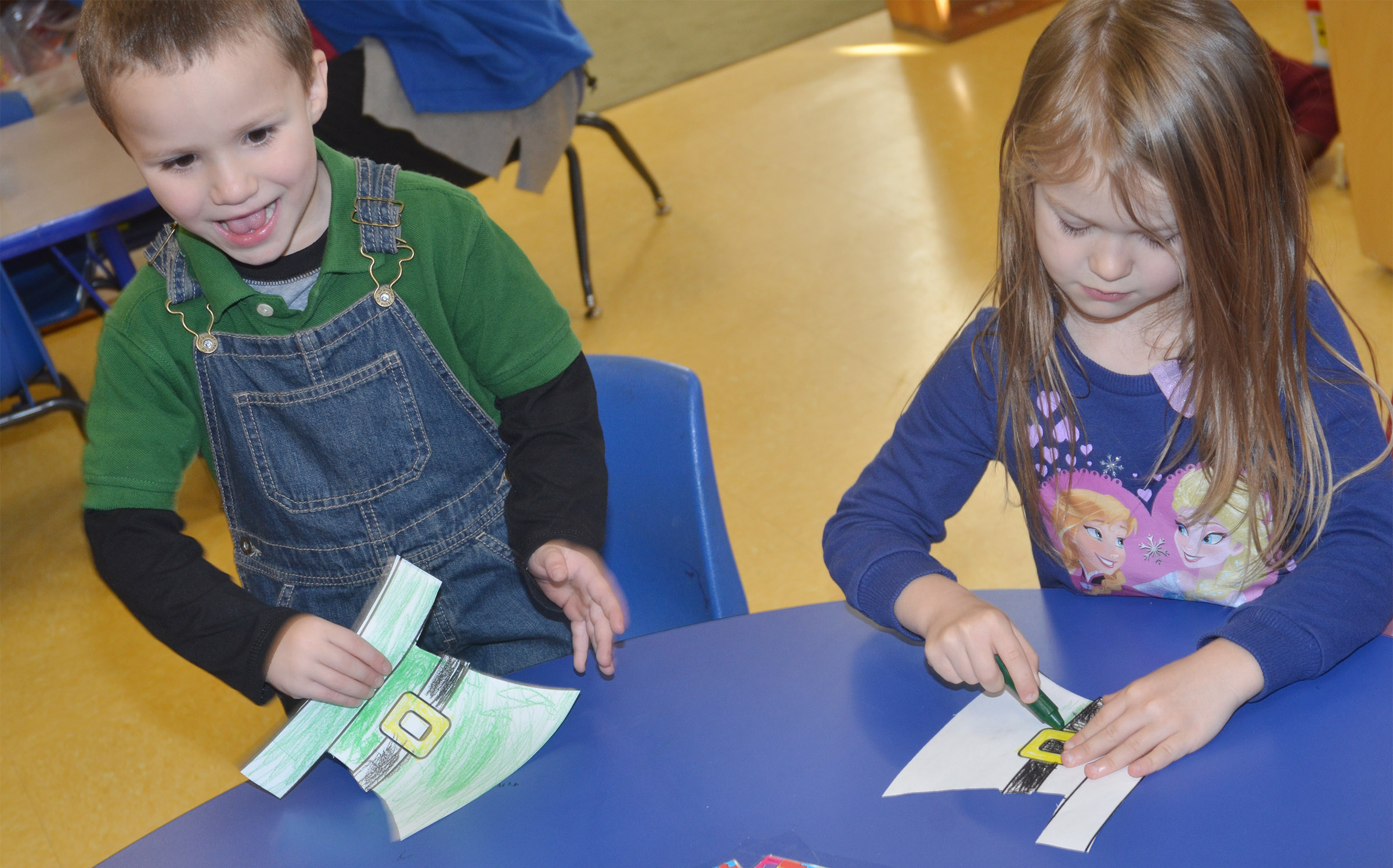 CES preschool students Triton Bradshaw, at left, and Lilly Spencer color their St. Patrick's Day hats.