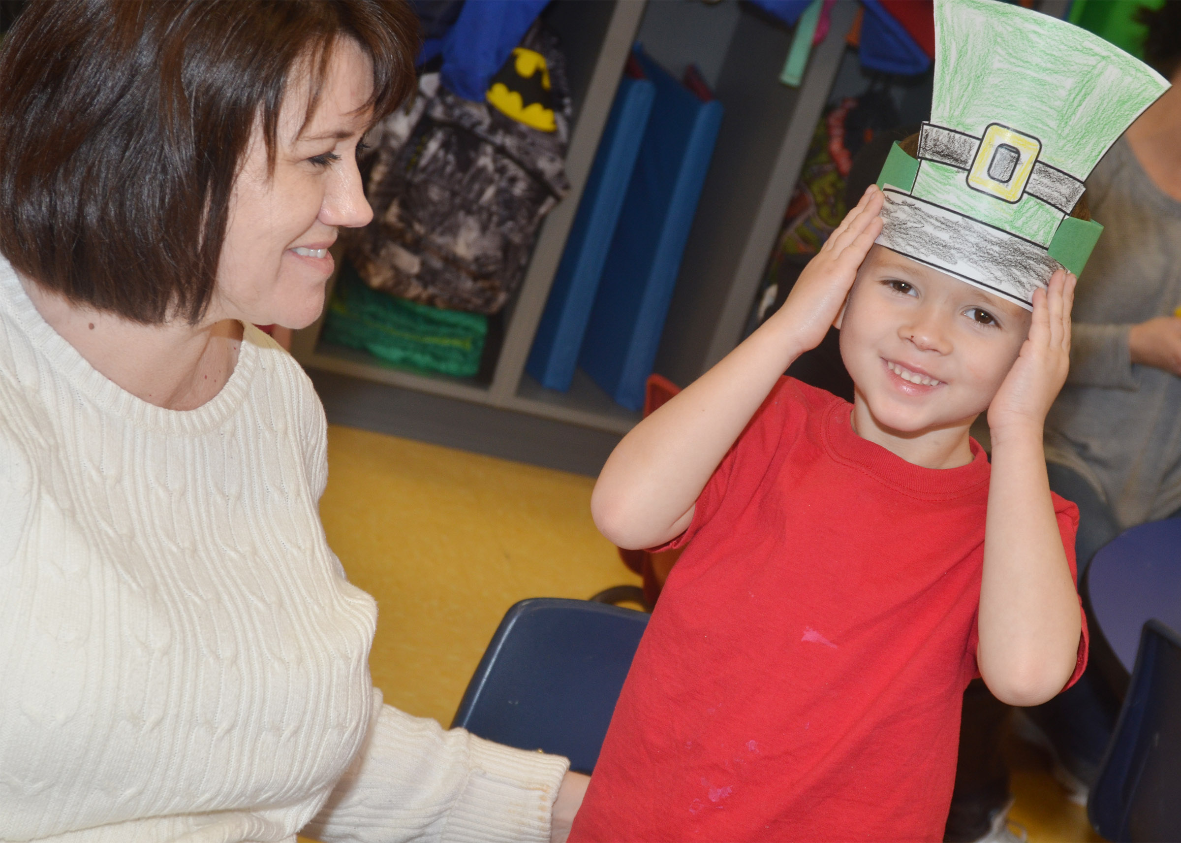 CES preschool student Andrew Stout smiles as he wears his St. Patrick's Day hat, with some help from teacher Denise Spencer.