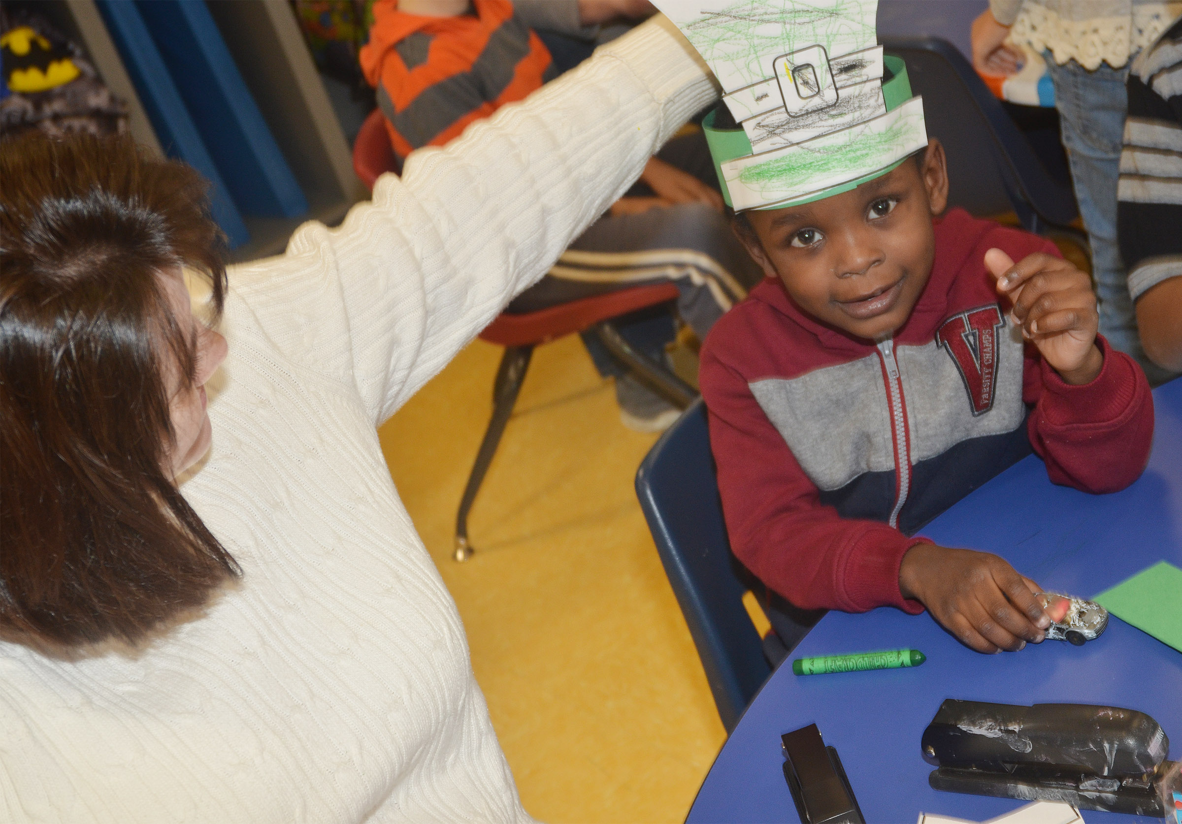 CES preschool teacher Denise Spencer helps Xavien Smith put on his St. Patrick's Day hat.