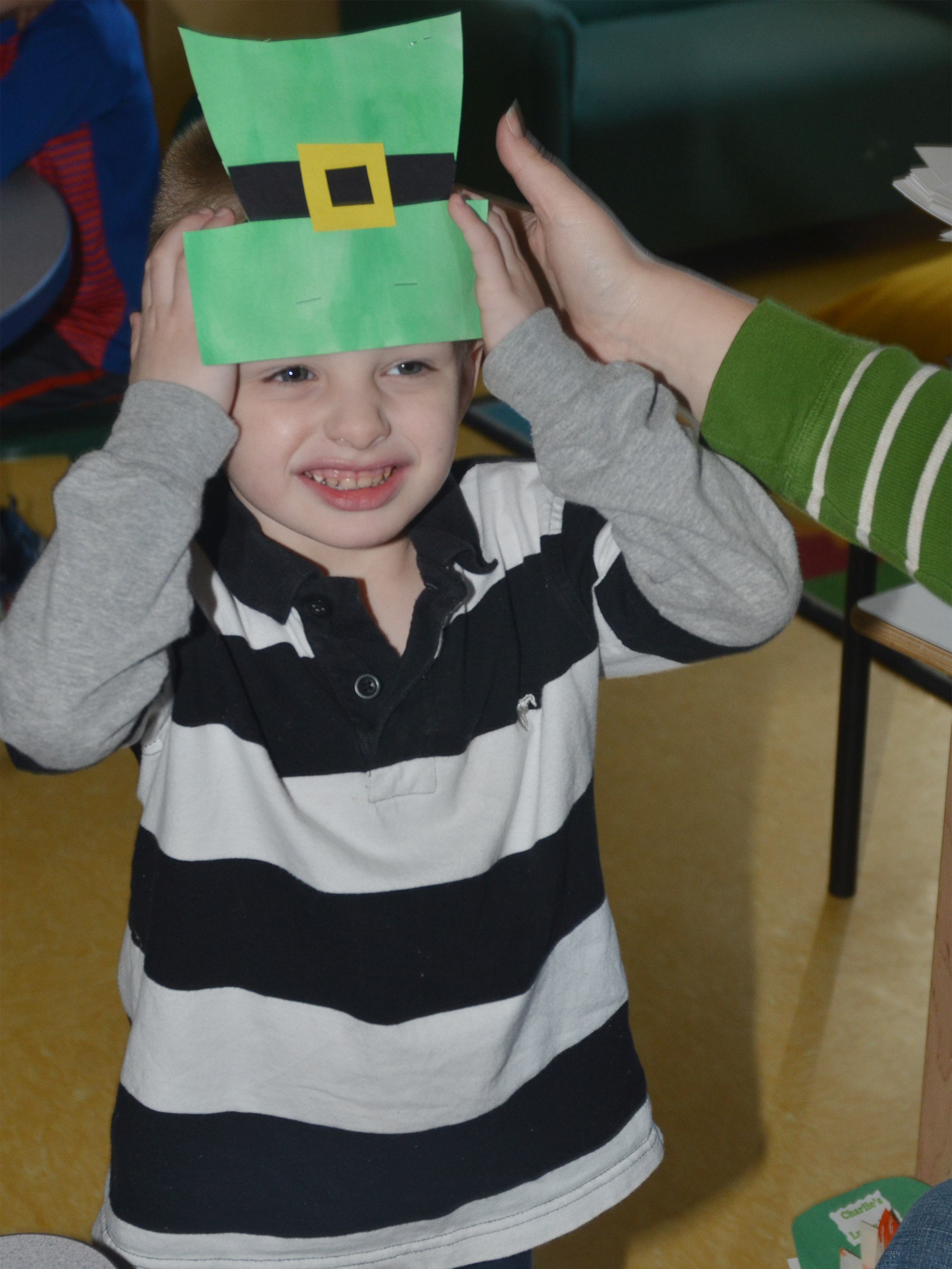 CES preschool student Nevon Stum smiles as he puts on his St. Patrick's Day hat.