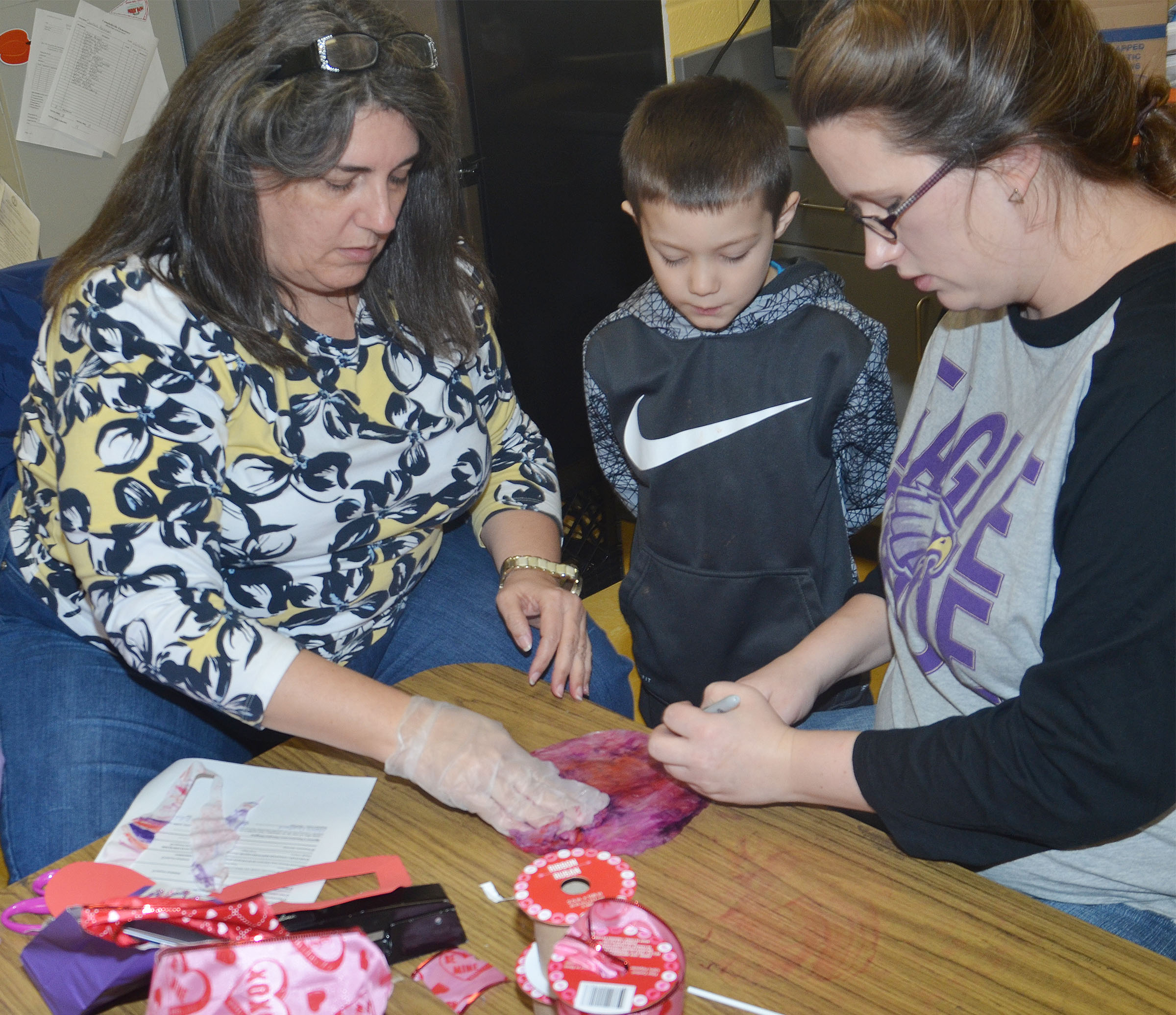 CES preschool teacher Sherry Cowherd, at left, and assistant Jessica Williams help Levi Ritchie add water to his colored coffee filter.