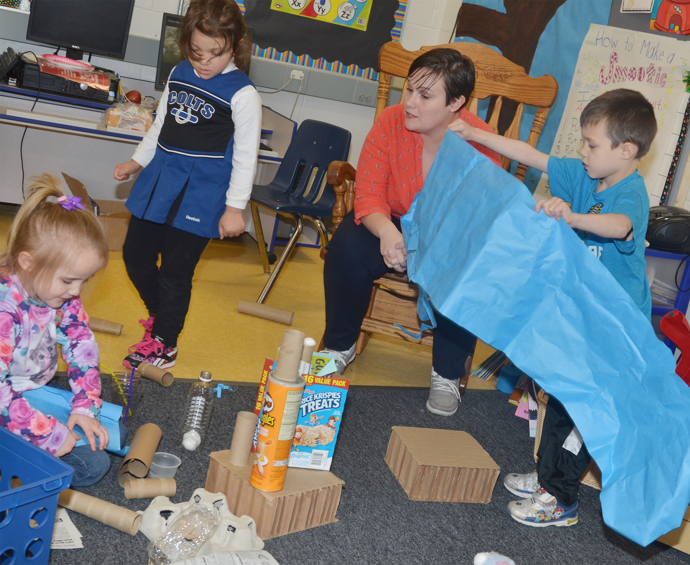 CES Wings Express Director Amanda Barnett watches as preschool students, from left, Trinity Dye, Addisyn Taylor and Levi Ritchie use everyday objects to build.
