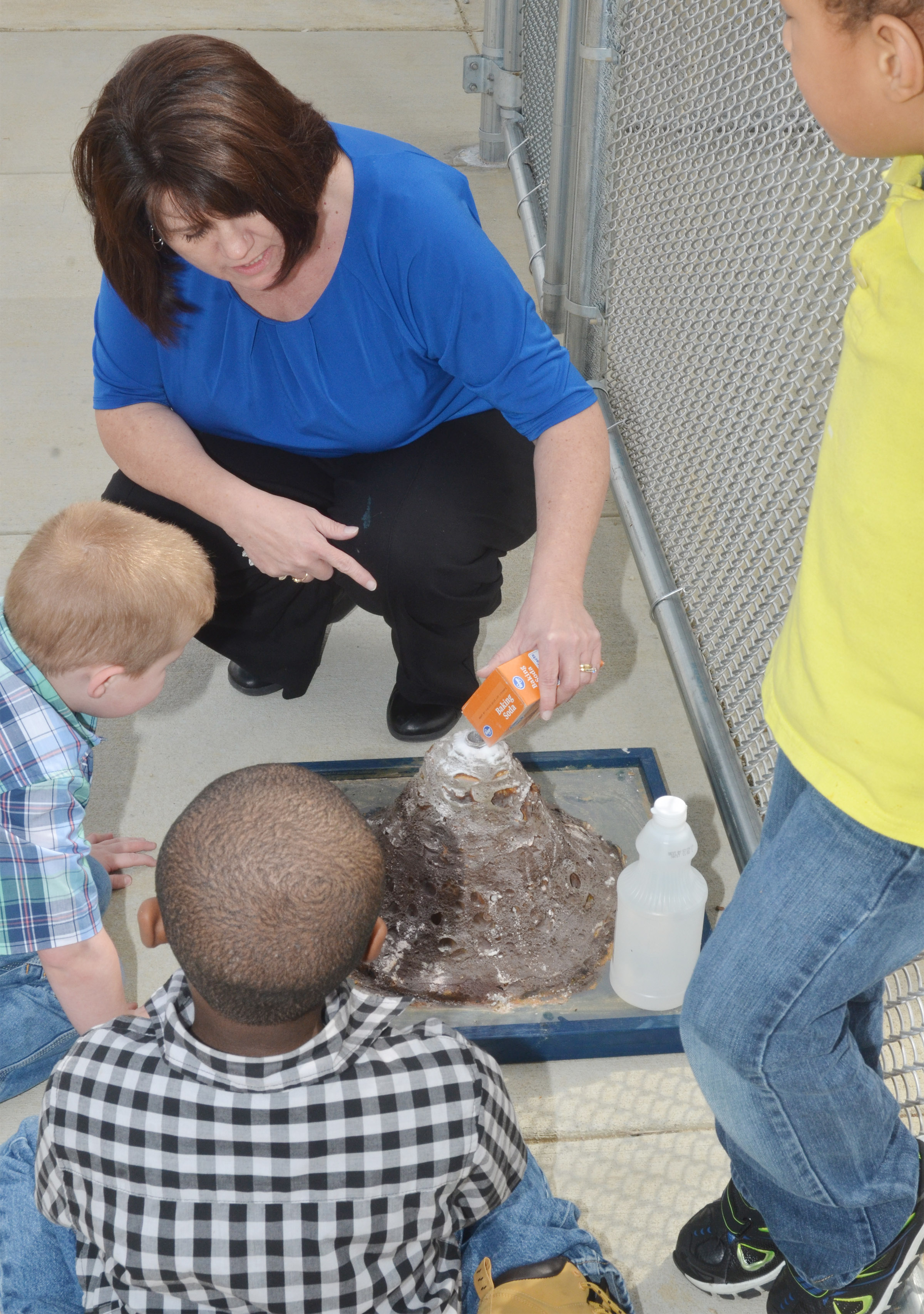 CES preschool teacher Denise Spencer adds baking soda to the volcano.