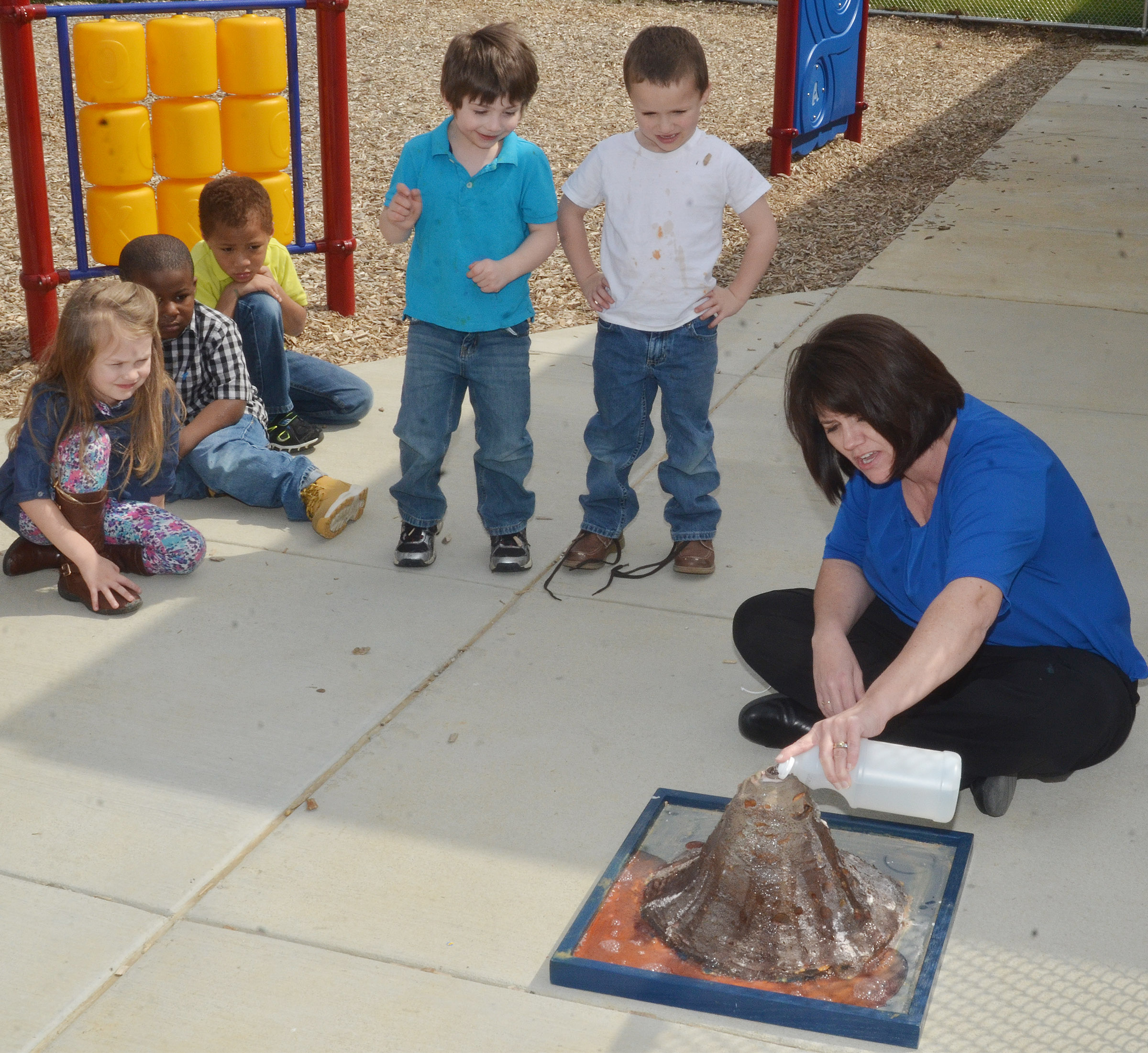 CES preschool teacher Denise Spencer adds vinegar to make the volcano erupt.