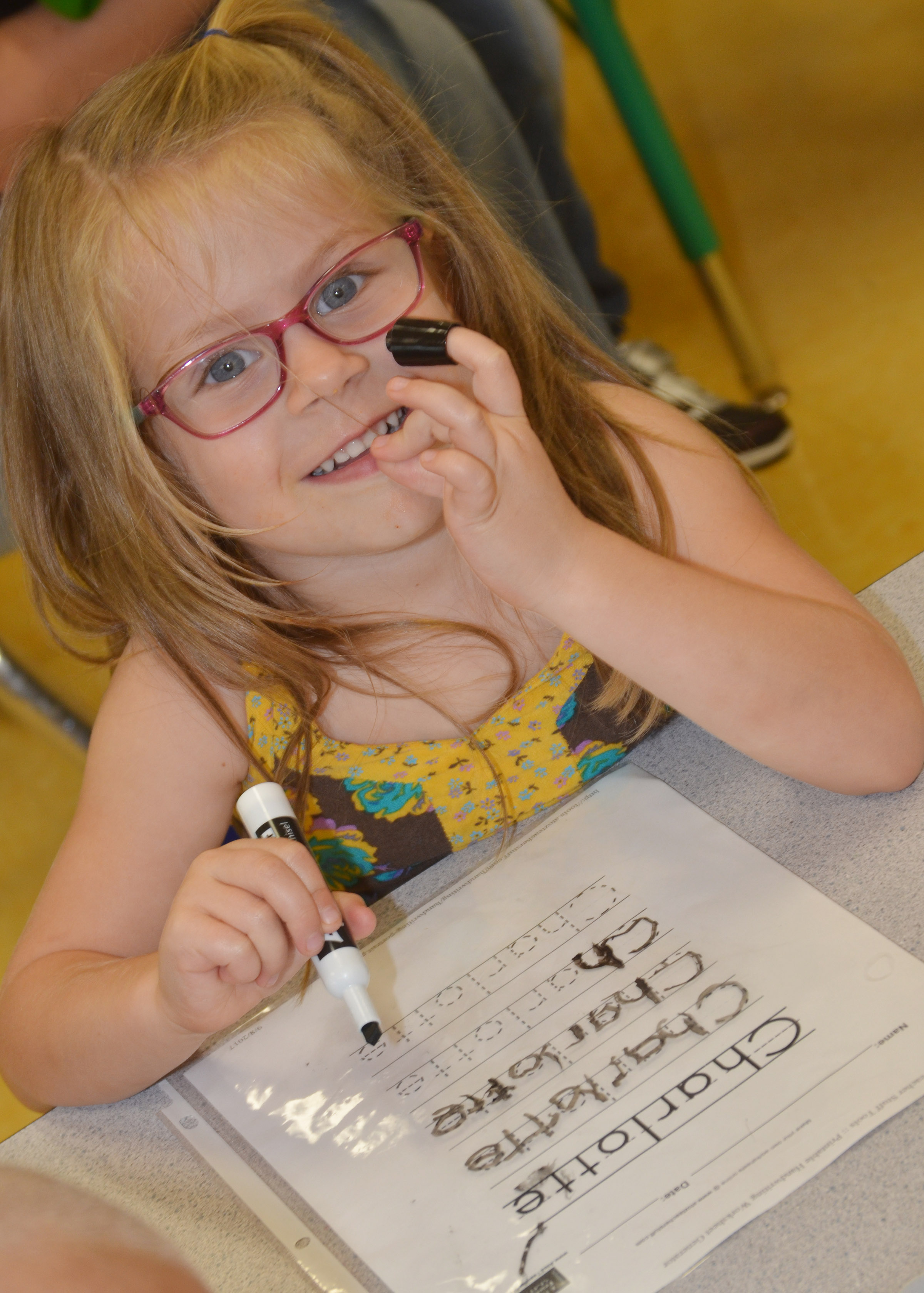 CES preschool student Charlotte Coots practices writing her name.