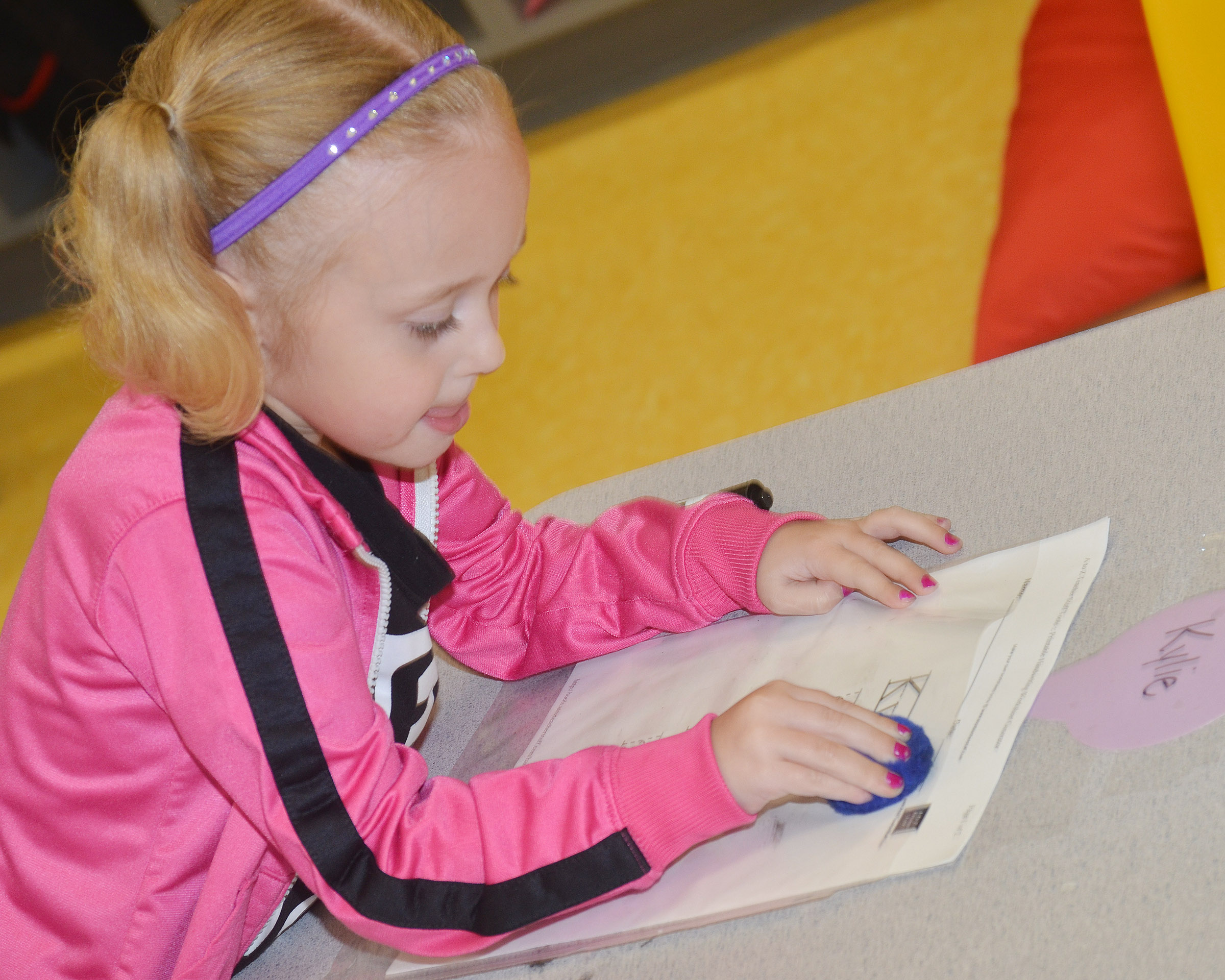 CES preschool student Kylie Thompson practices writing her name.